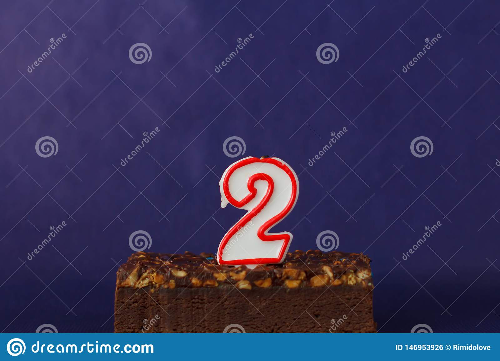 Happy Birthday Brownie Cake with Peanuts, Salted Caramel and Unlighted Candles on the Violet Background. Copy Space for Text.