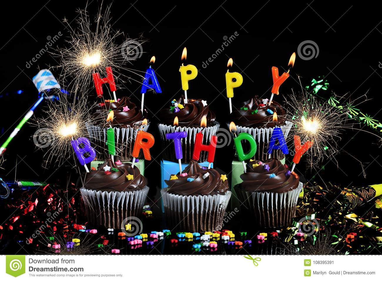 Chocolate Cupcakes With Lit Candles Spelling Happy Birthday Colorful Star Candies On And Surounding Black Surface Gold Sparklers H