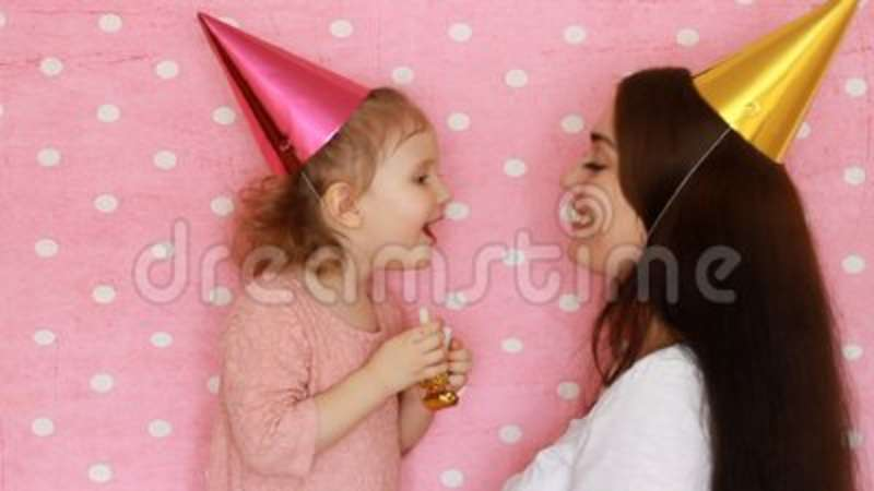 Happy Birthday Mother And Daughter In Holiday Caps Blowing Horns Smiling And Laughing Woman And Child Having Fun And