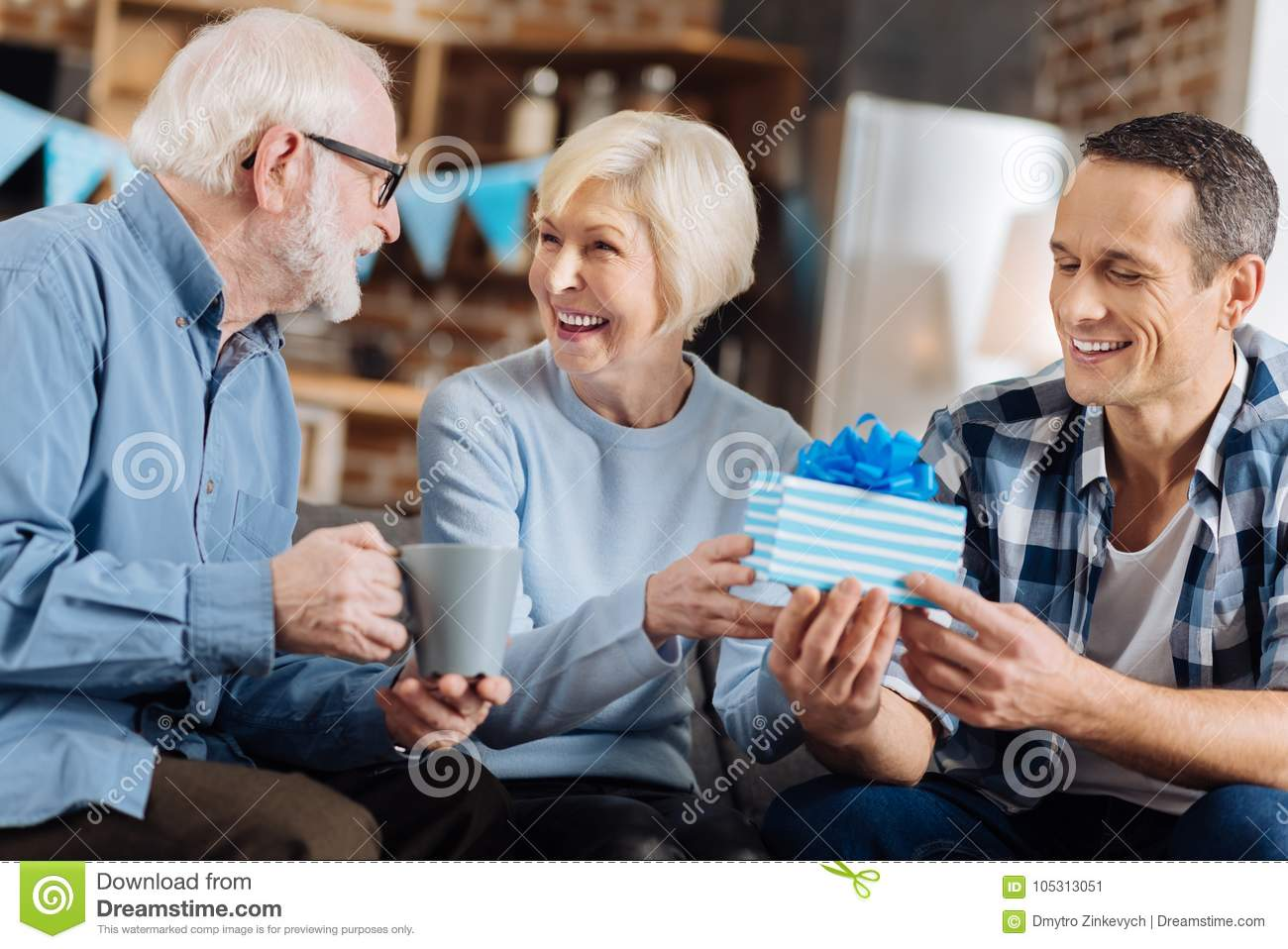 Happy Birthday Upbeat Young Men Sitting On The Sofa Next To His Elderly Parents And Giving A Present Mother While She Sharing Happiness