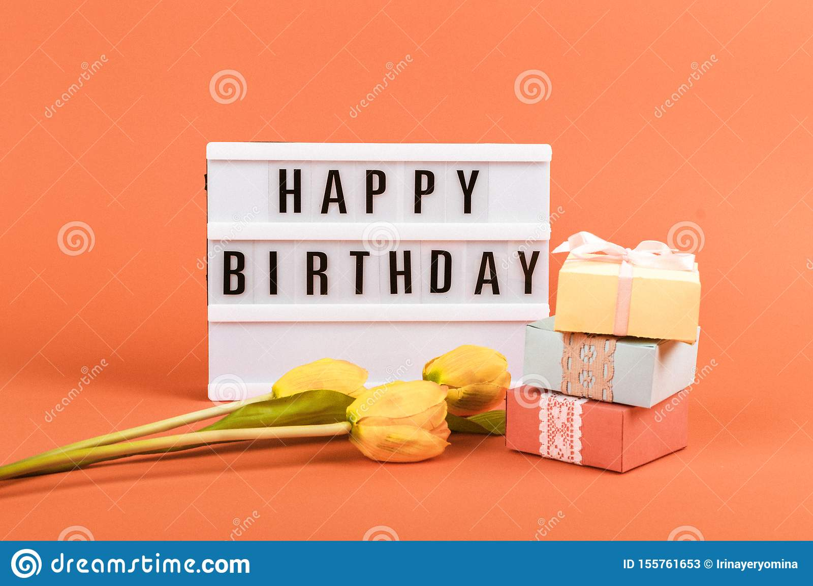Happy birthday word light box, Yellow tulips flowers, gift boxes on coral background. Festive Greeting birthday background