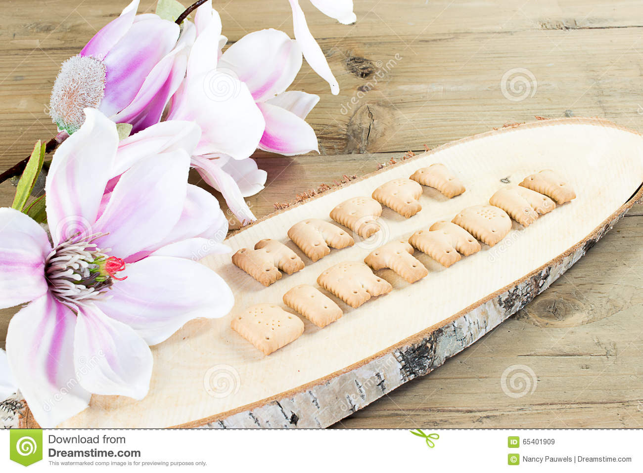 letter collage with alphabet cookies happy birthday card with words on wooden background white and purple magnolia flower as decoration