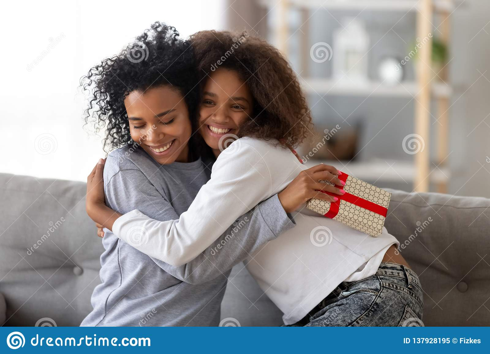 Daughter Hugging On Couch At Home Smiling Black Teenage Girl Congratulate Happy Mom Special Occasion Embrace Making Surprise Present Birthday Gift