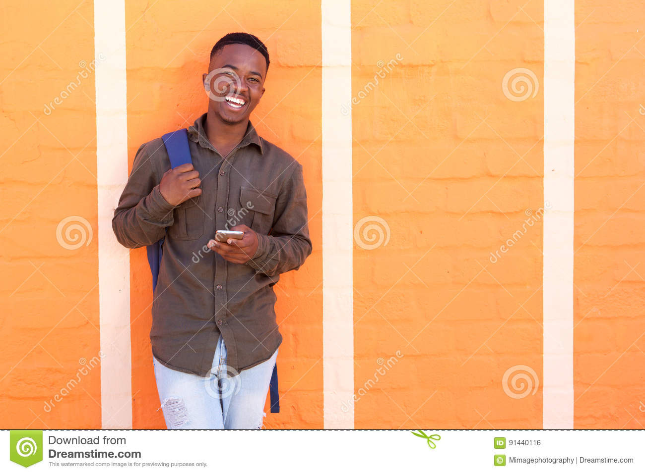 Happy black guy laughing with cell phone against orange wall