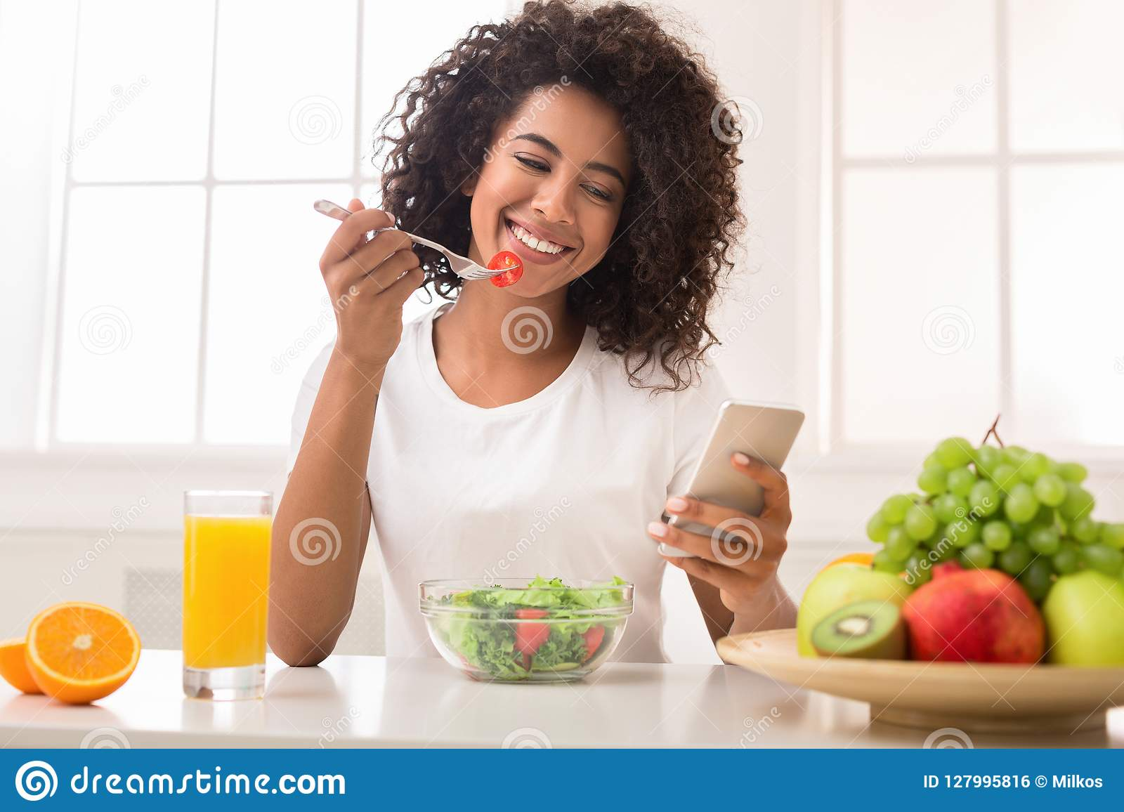 Happy black woman texting on smartphone while eating salad