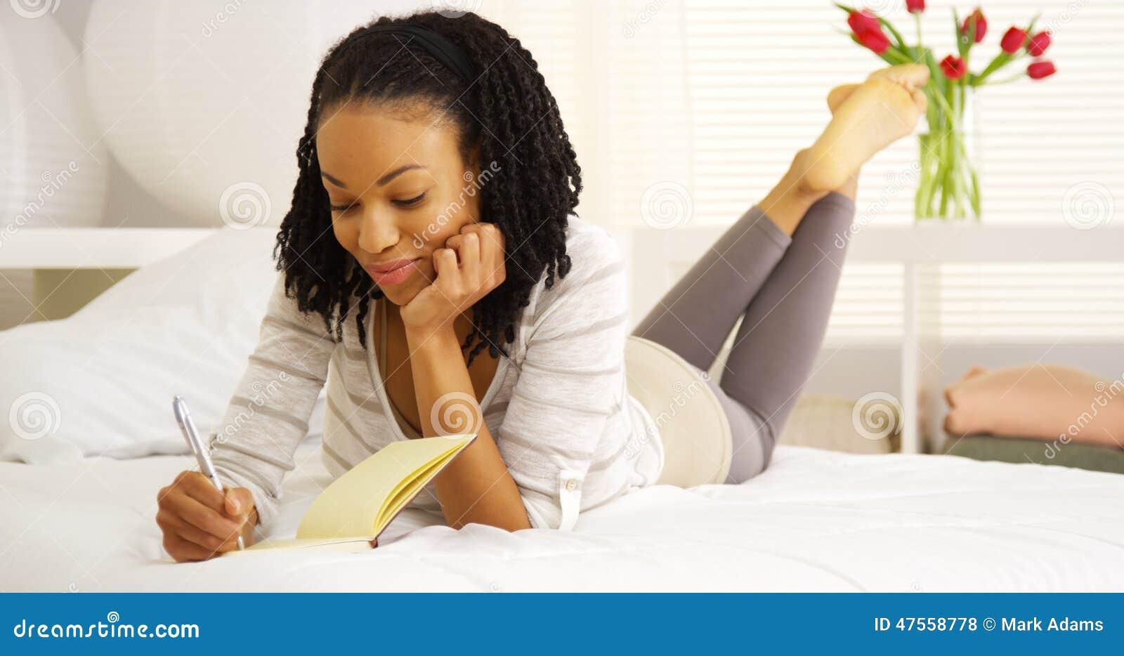 Happy black woman writing in journal