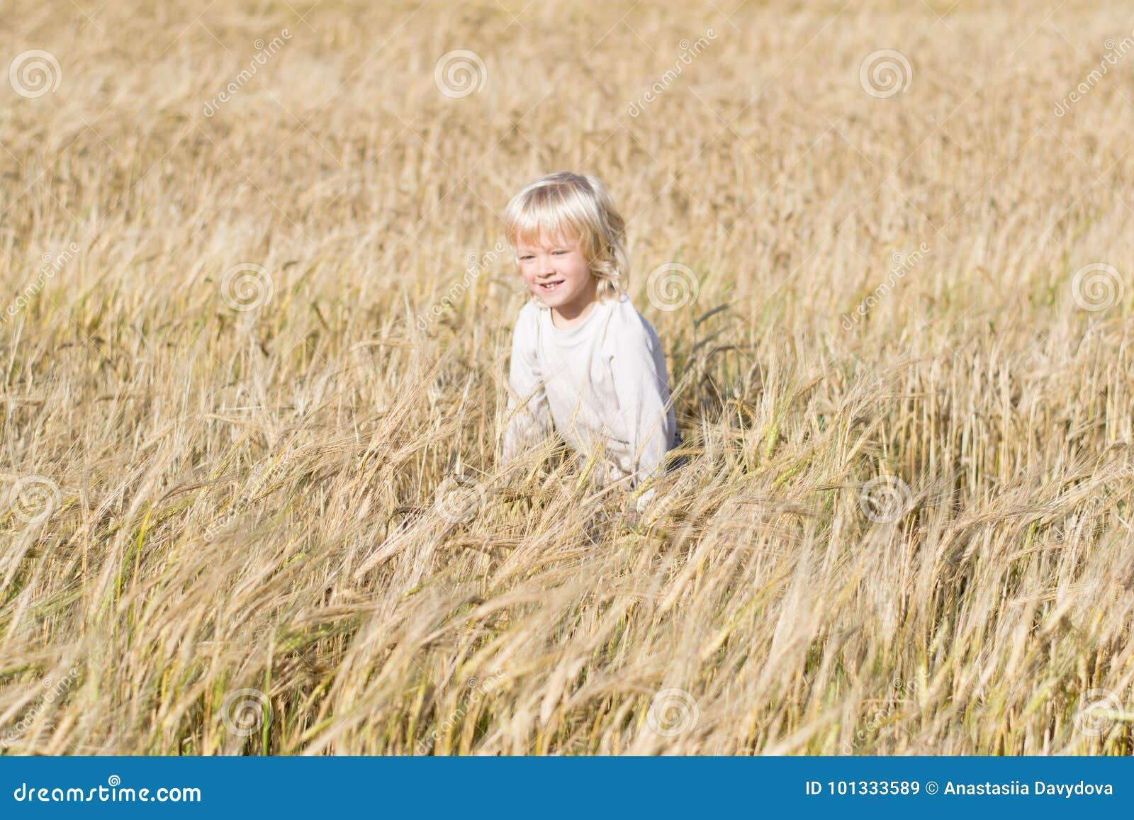 Happy blond child has fun in the rye field