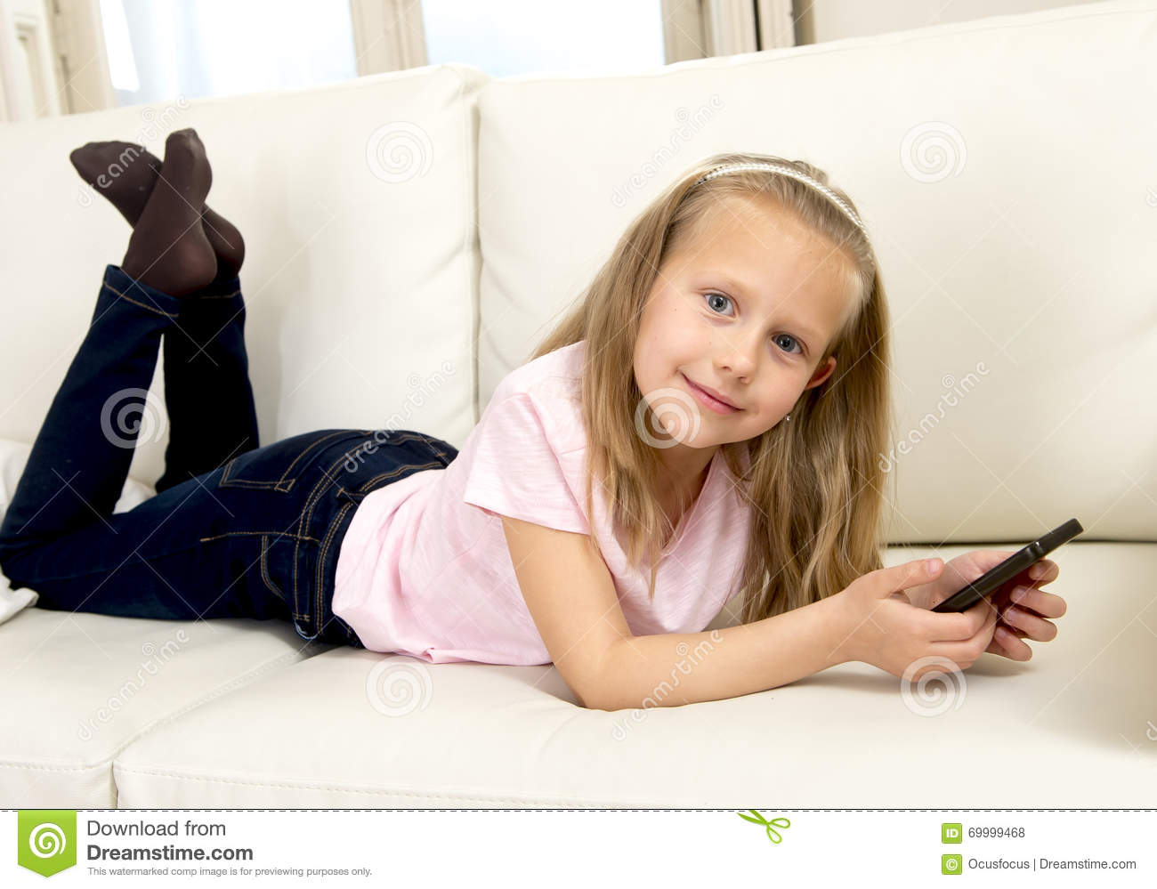 Happy blond little girl on home sofa using internet app on mobile phone