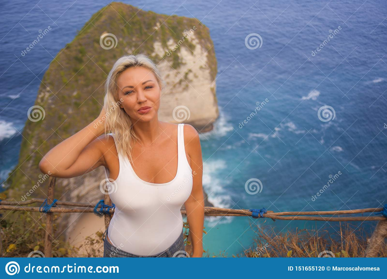 Happy blond tourist woman feeling free on the stunning view of beautiful sea cliff beach at viewpoint enjoying exotic Summer