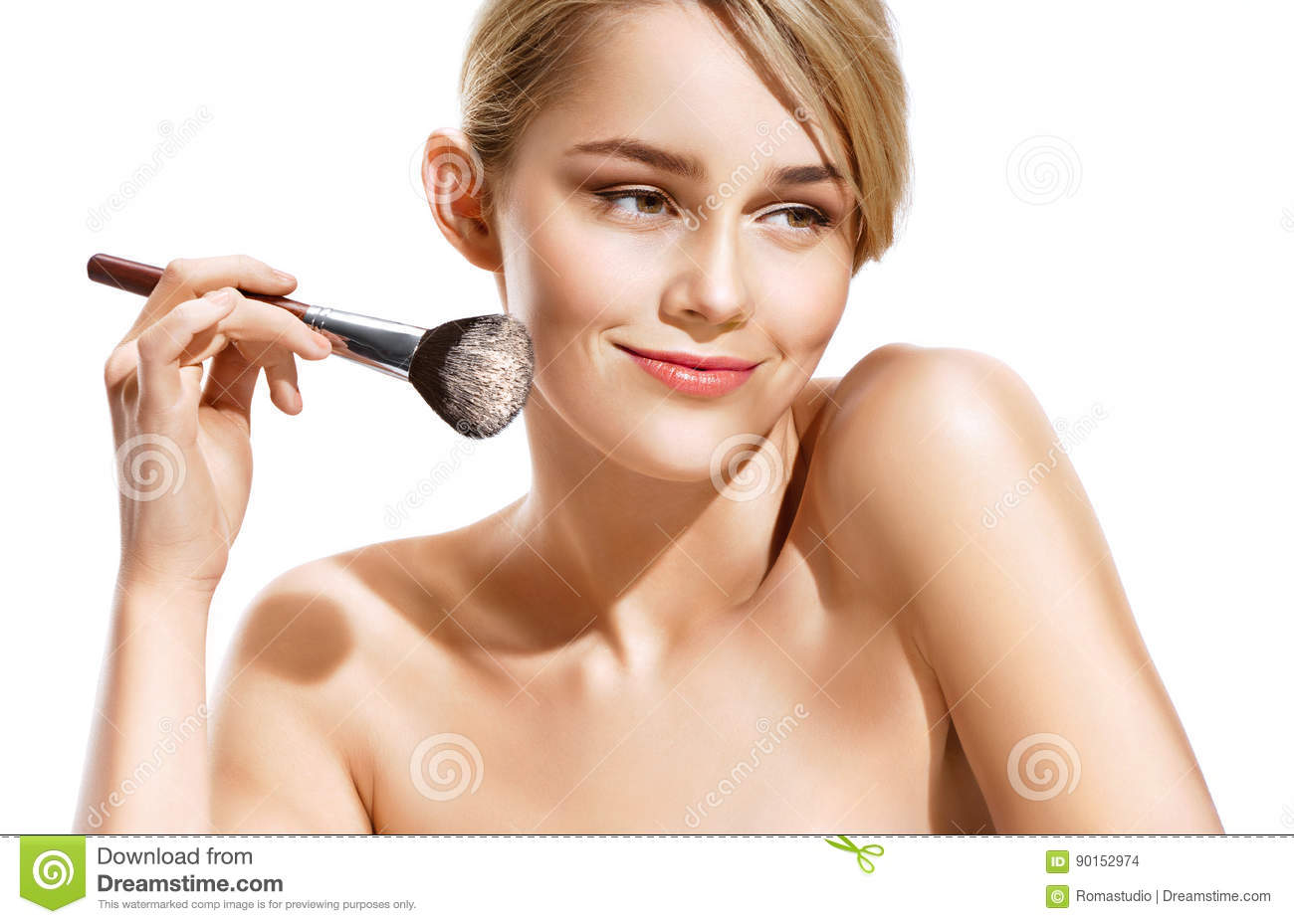 Happy blonde applying dry cosmetic tonal foundation on the face using makeup brush.