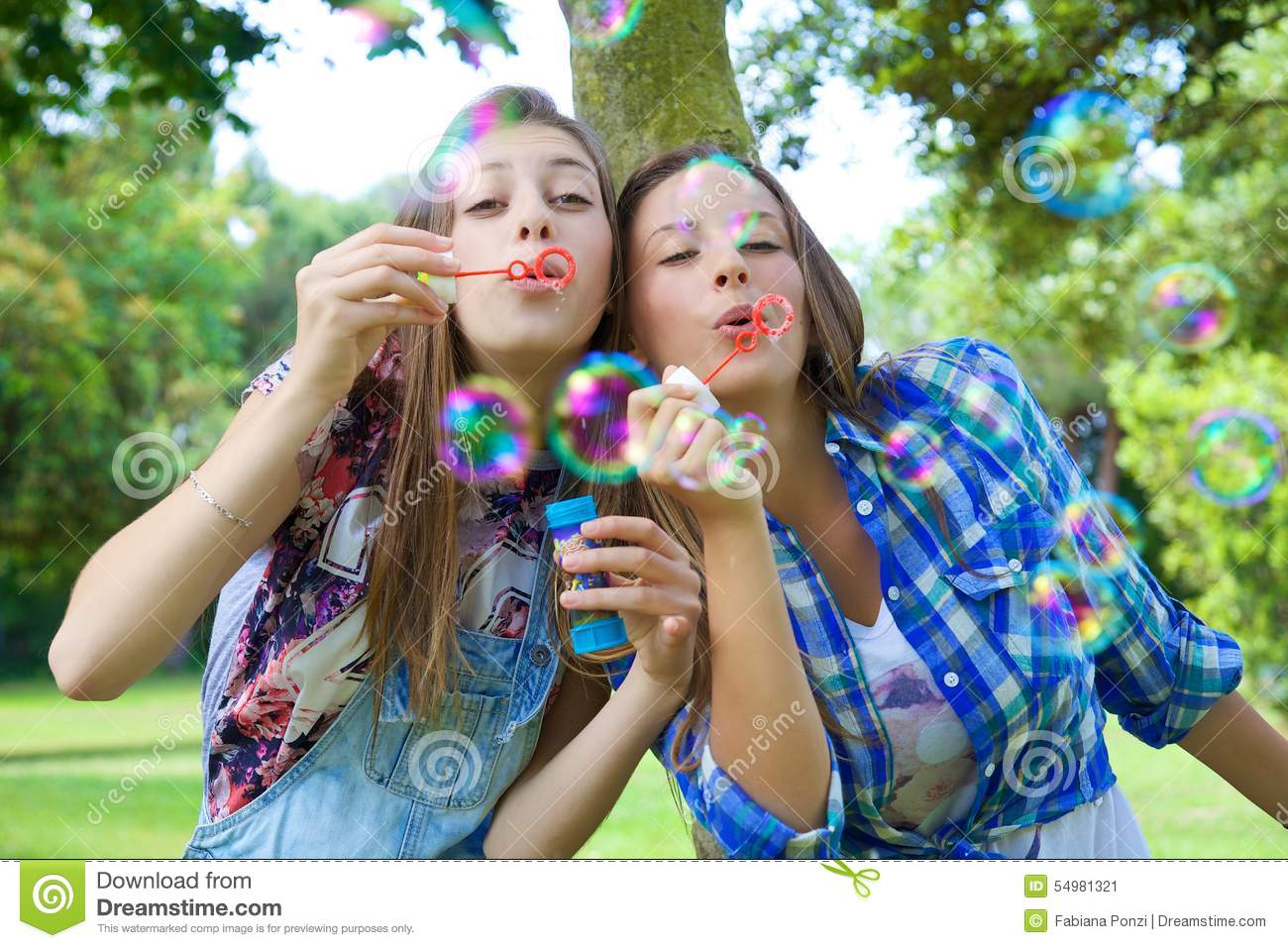 Happy Blonde Sisters Having Fun Blowing Soap Bubbles In