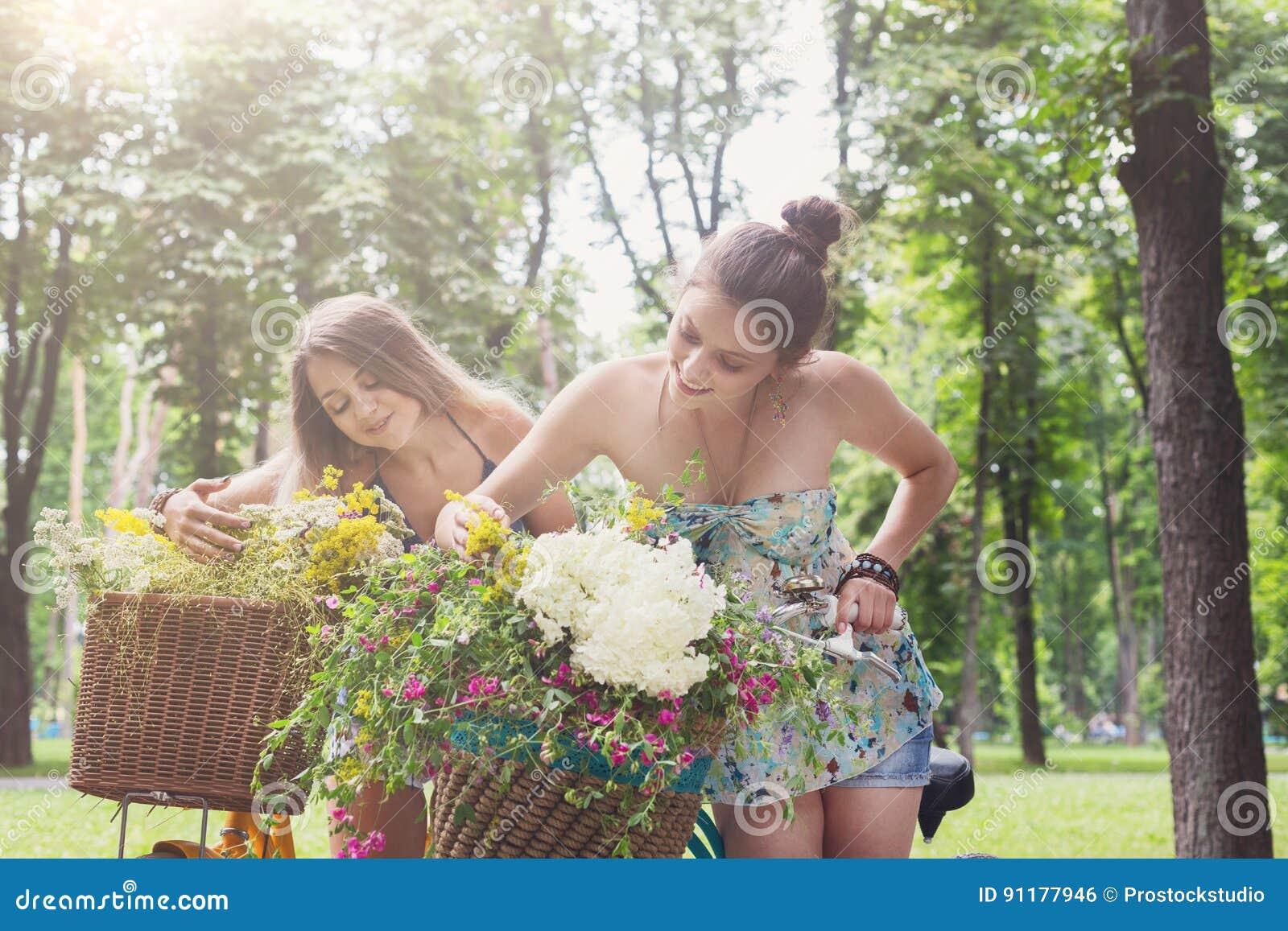 Happy boho chic girls gather wild flowers on bicycle ride