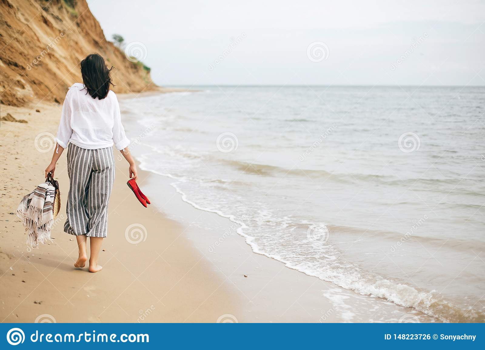 Happy boho woman relaxing at sea, enjoying walk on tropical island. Stylish hipster girl walking barefoot on beach, holding bag