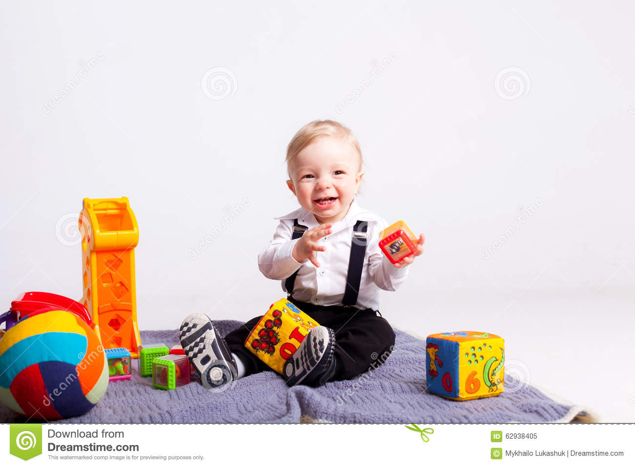 Boy Toys Blue : Happy boy on blanket with toys white background stock