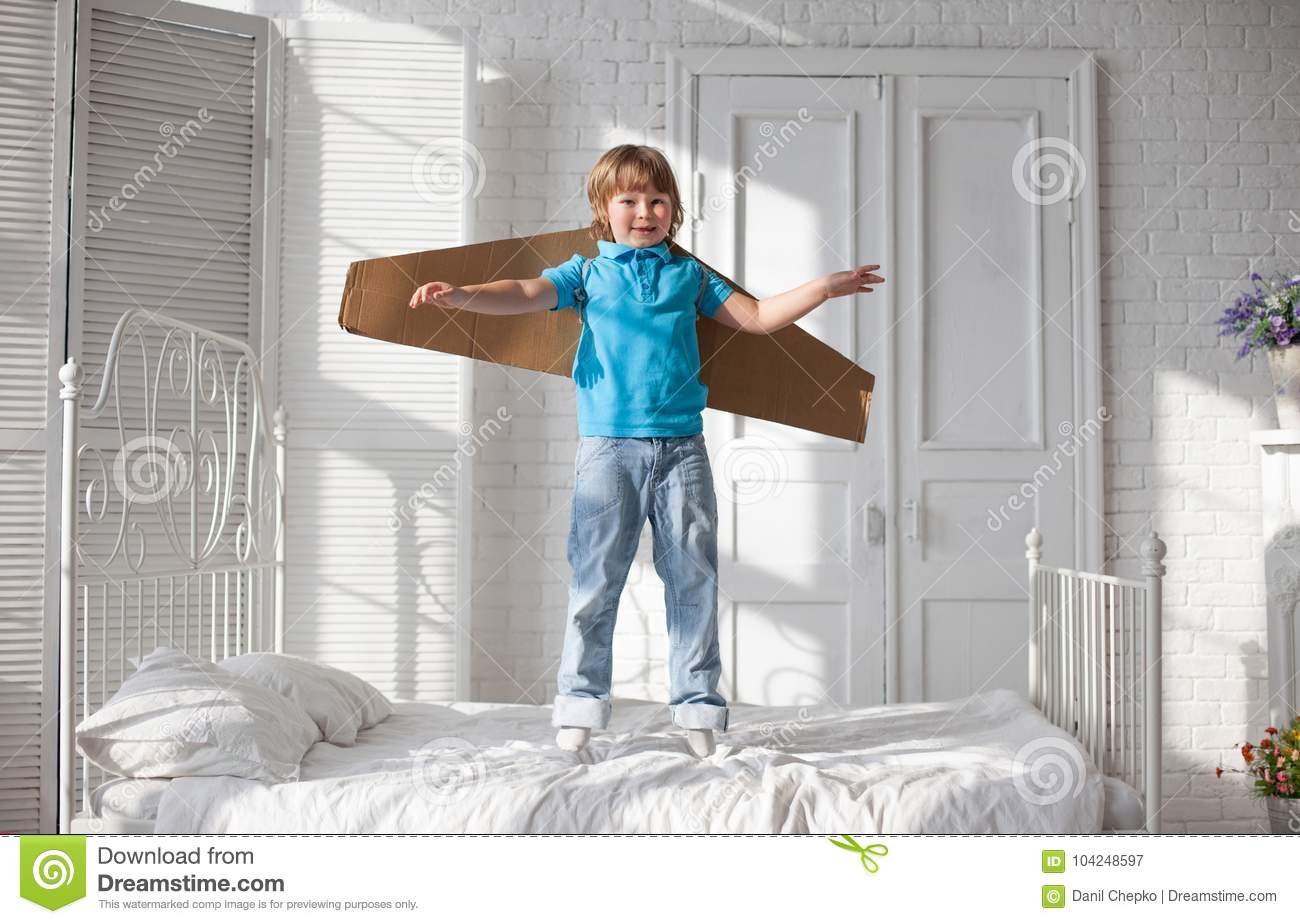 Happy boy with cardboard boxes of wings in home dream of flying
