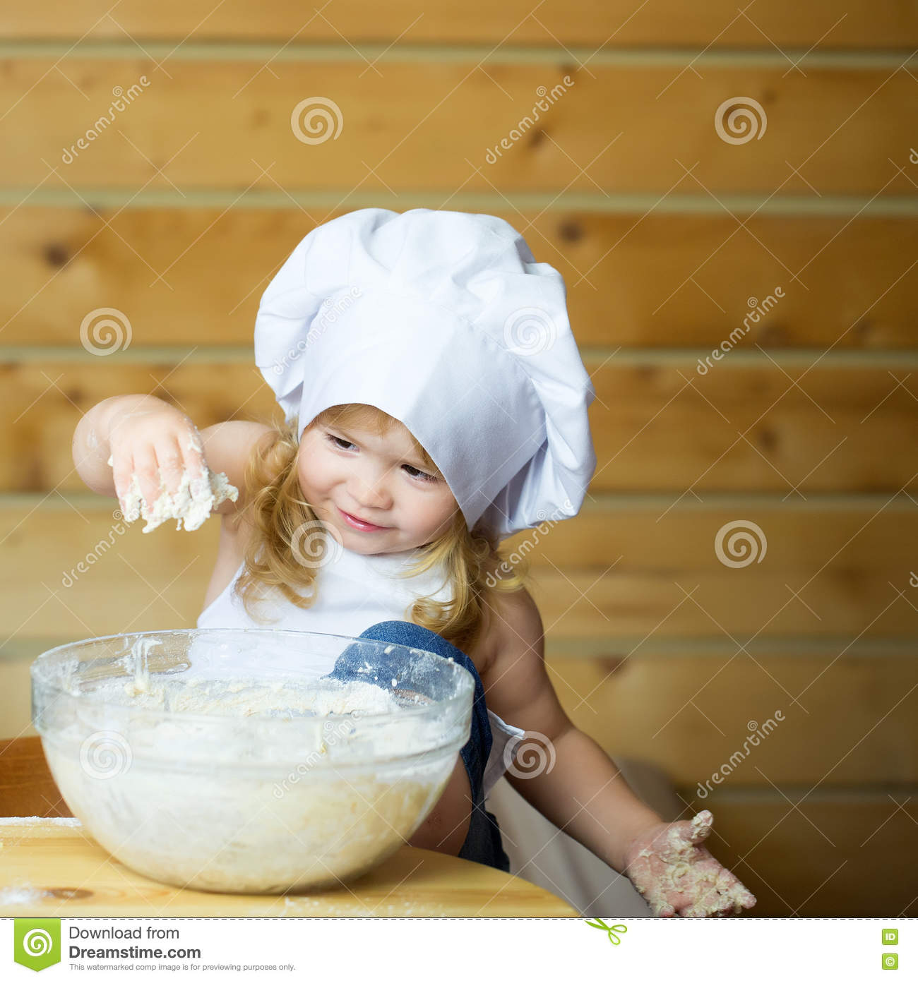 4a4c92efe Small cute baby boy or child with happy face in white cook uniform with chef  hat and apron kneading dough with flour in glass bowl in kitchen on wooden  or ...