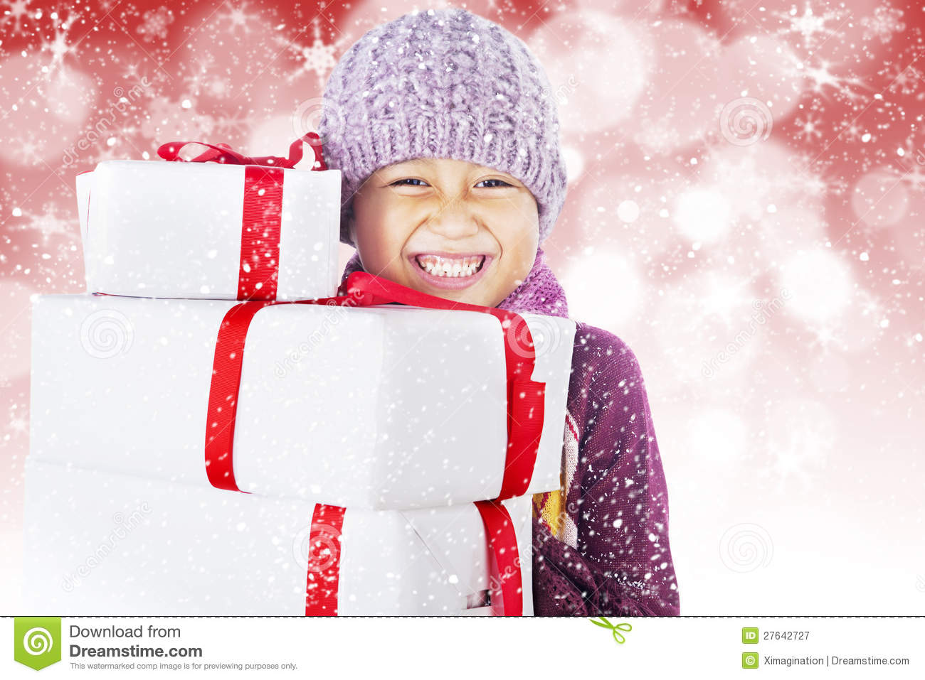 Happy boy with christmas boxes on defocused light