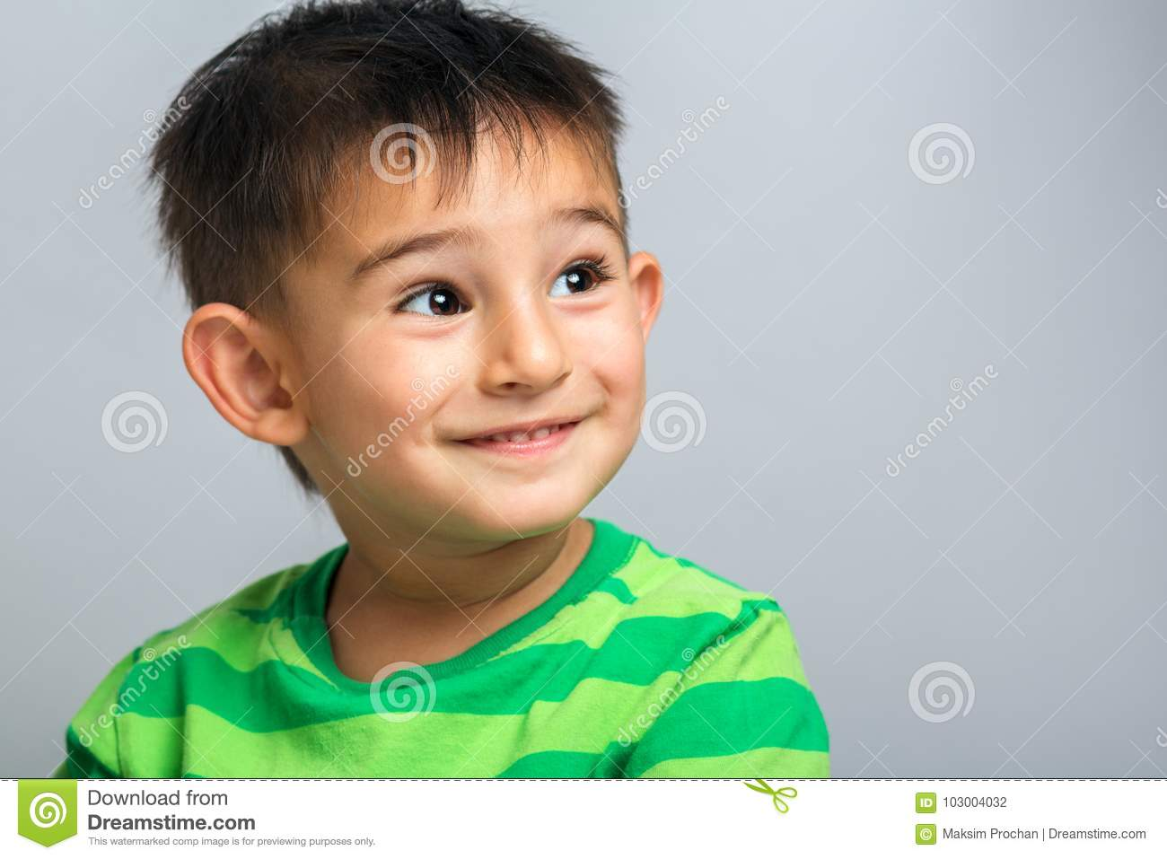 Happy boy face, portrait of a child on a gray background
