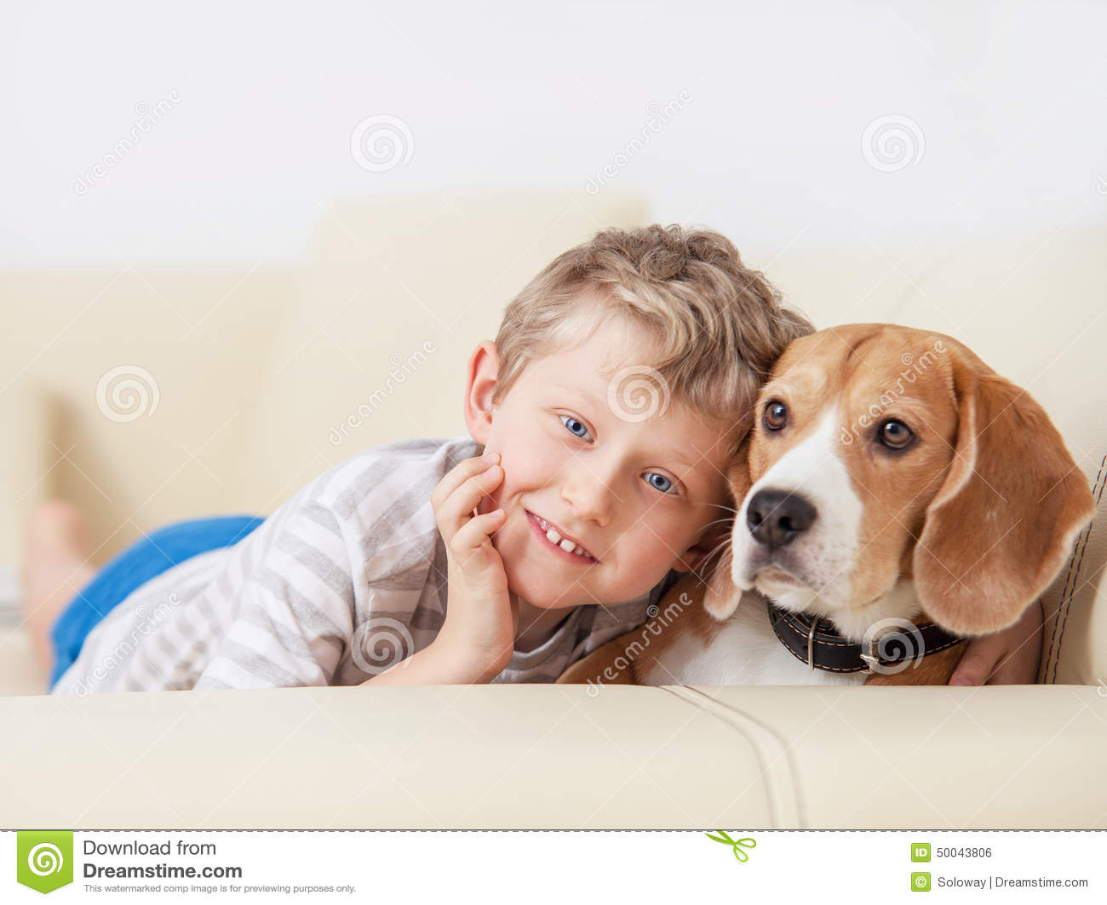 Happy Boy With His Dog Lying On Sofa Stock Photo Image