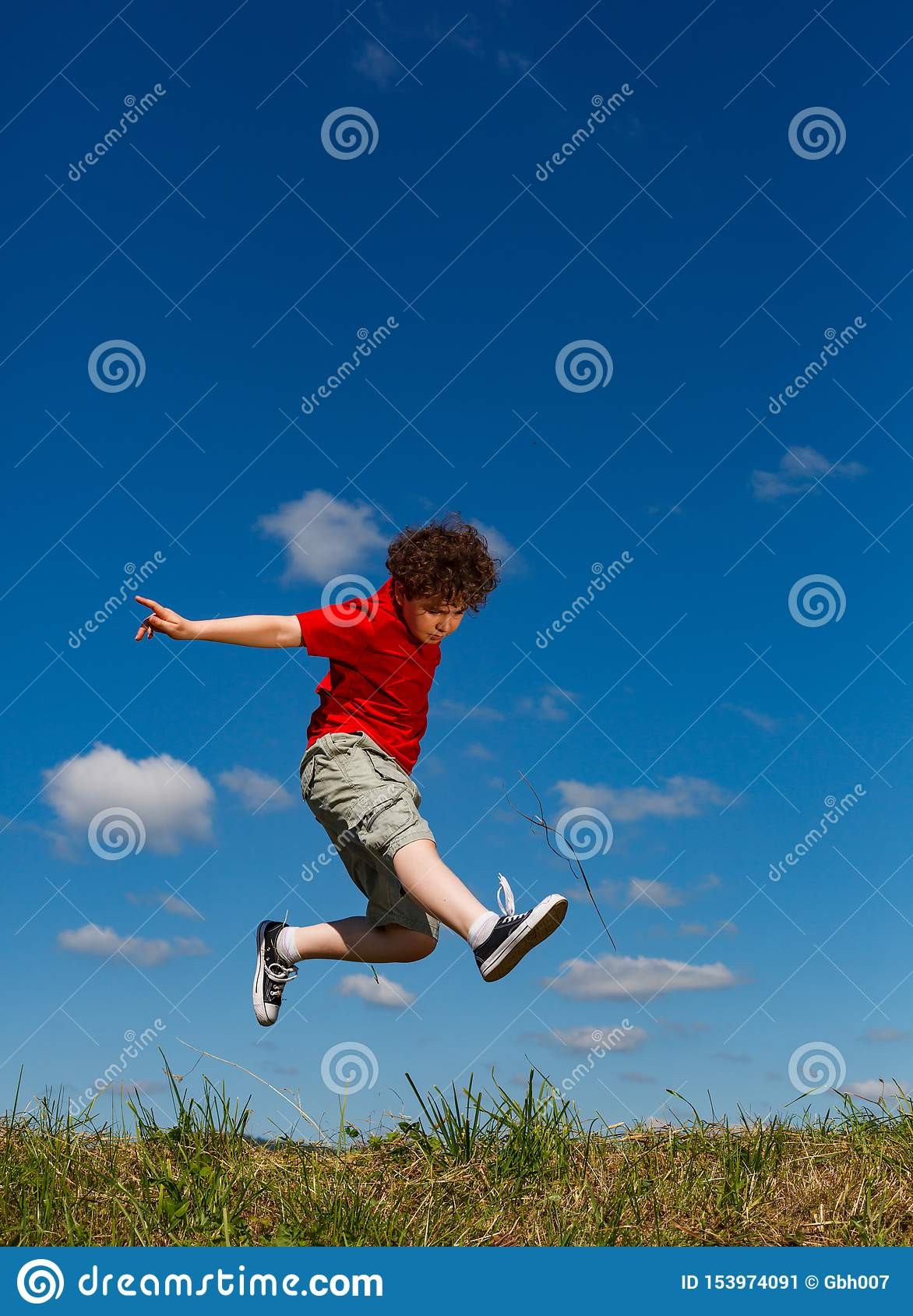 Boy jumping, running against blue sky