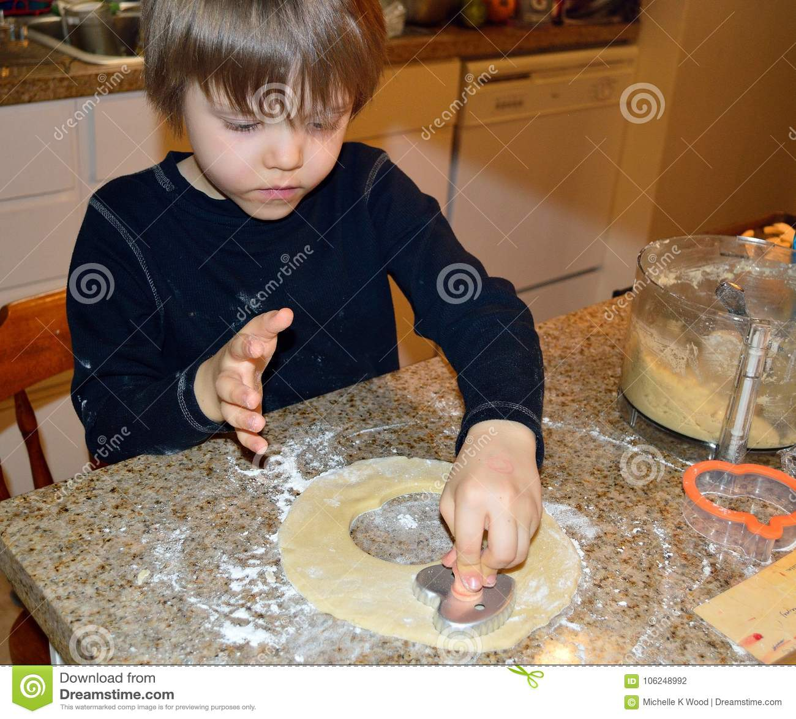 Happy boy making heart cookies
