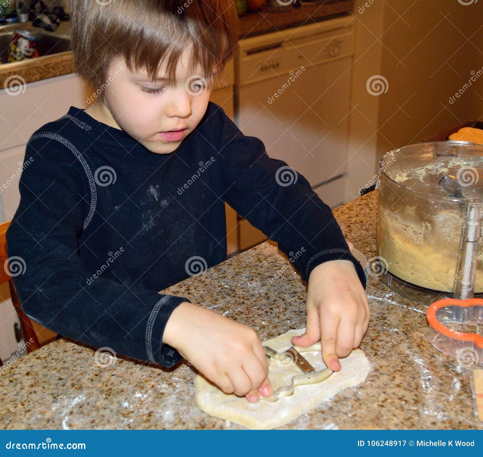 Happy boy making snowman cookies