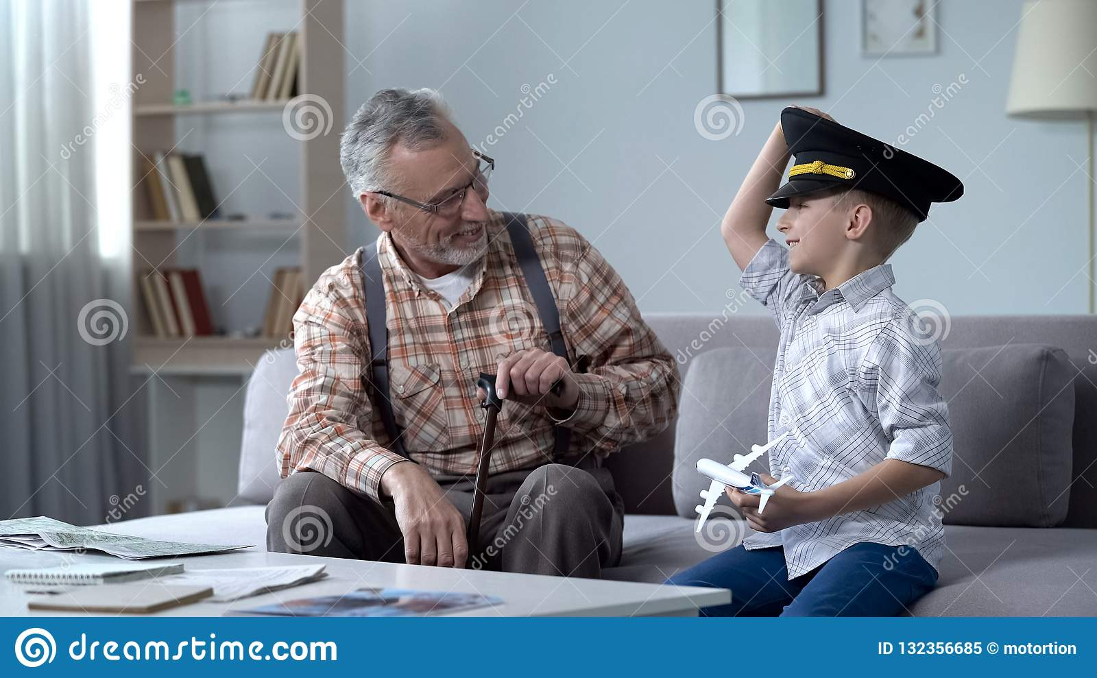 Happy boy playing with toy airplane, grandfather former pilot proud of grandson