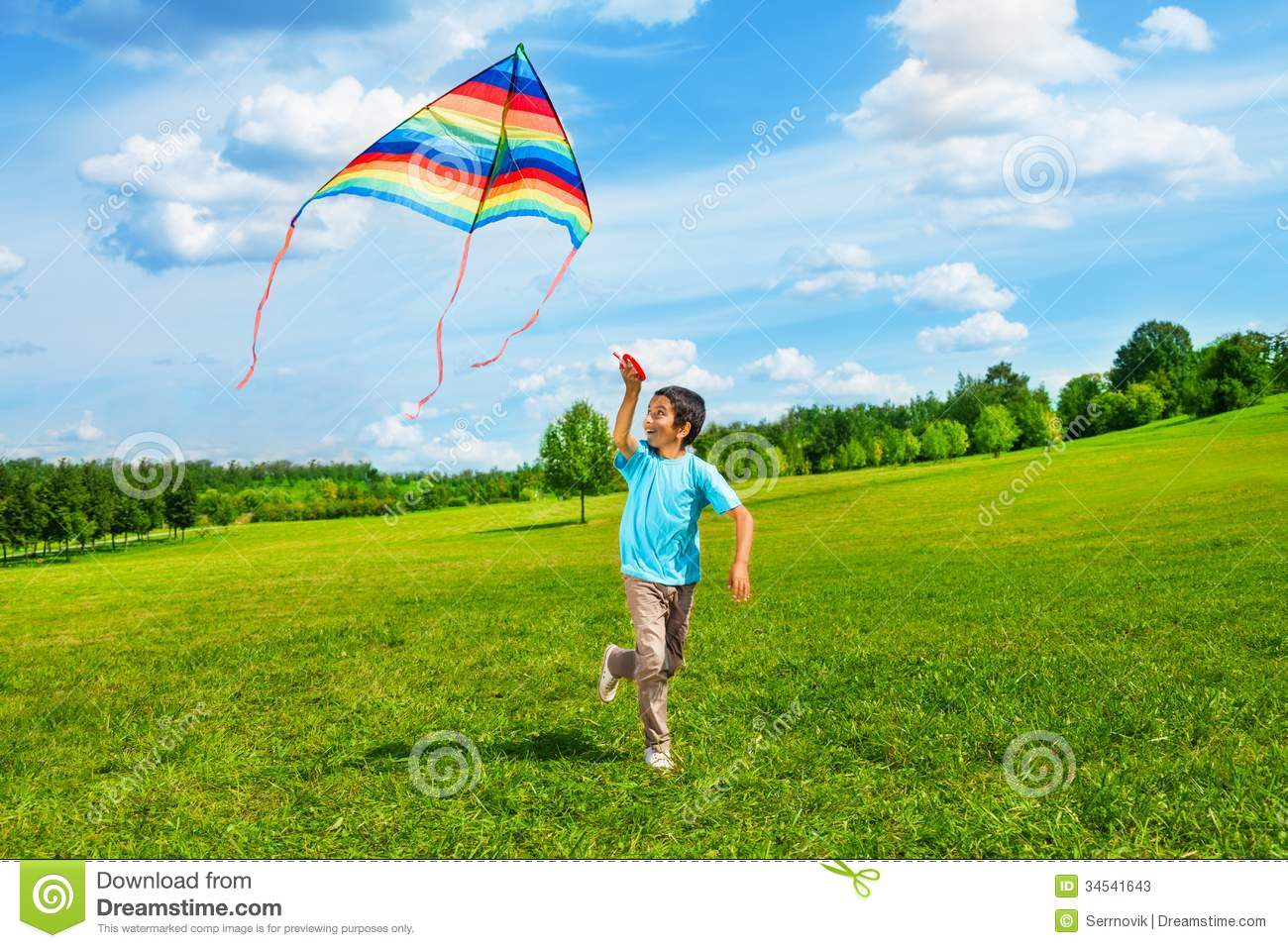 Little boy in blue shirt running with kite in the field on summer day ...