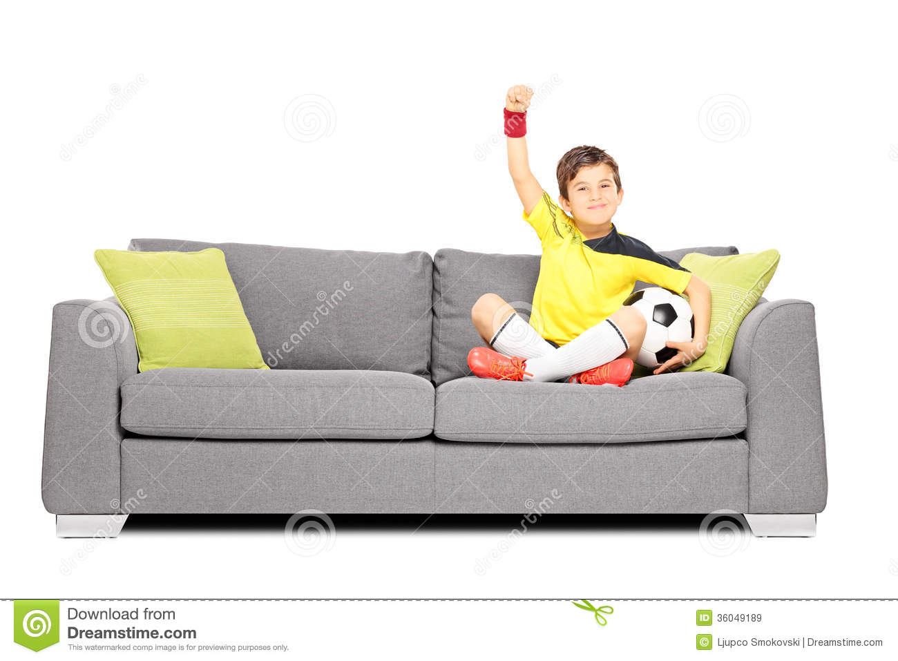 happy boy with a soccer ball sitting on a sofa and gesturing hap stock image image of athletic. Black Bedroom Furniture Sets. Home Design Ideas