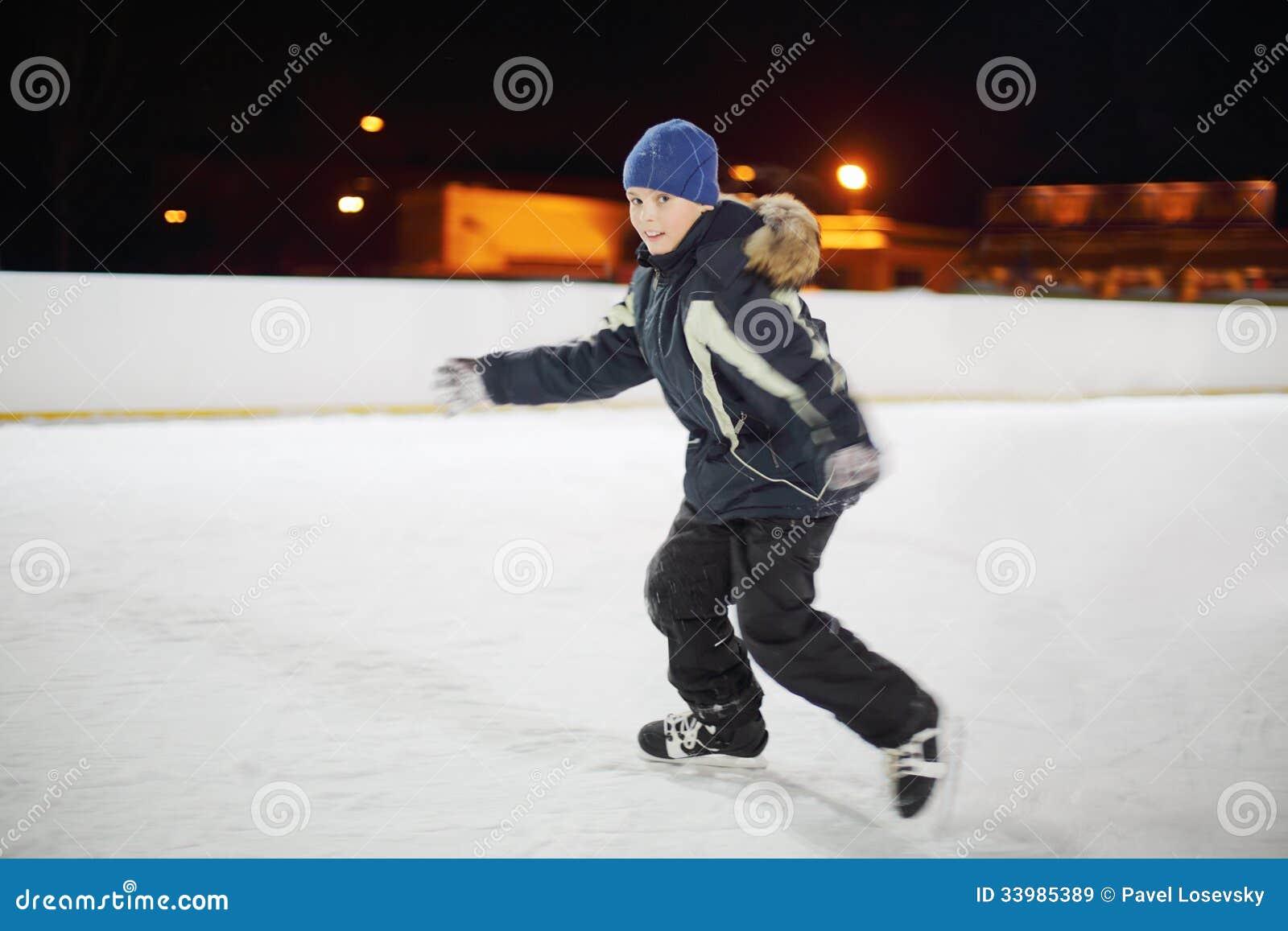 Happy boy wearing in black suit skates at night.