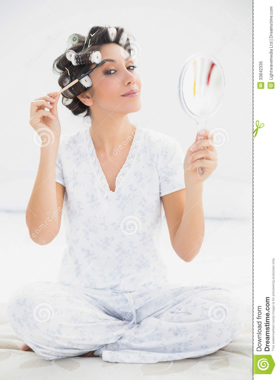 Happy Brunette In Hair Rollers Holding Hand Mirror And