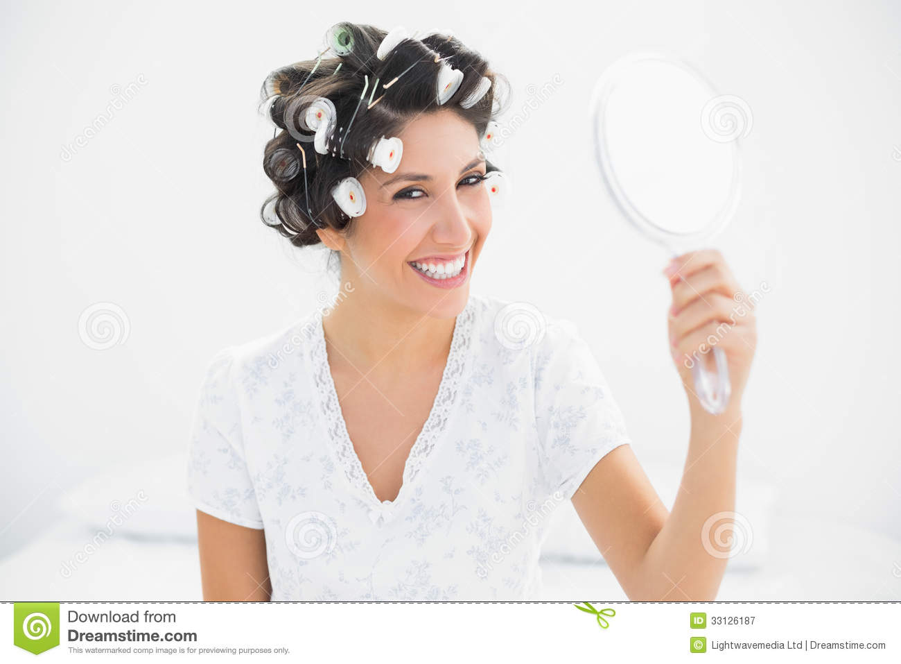 Happy Brunette In Hair Rollers Holding Hand Mirror Smiling
