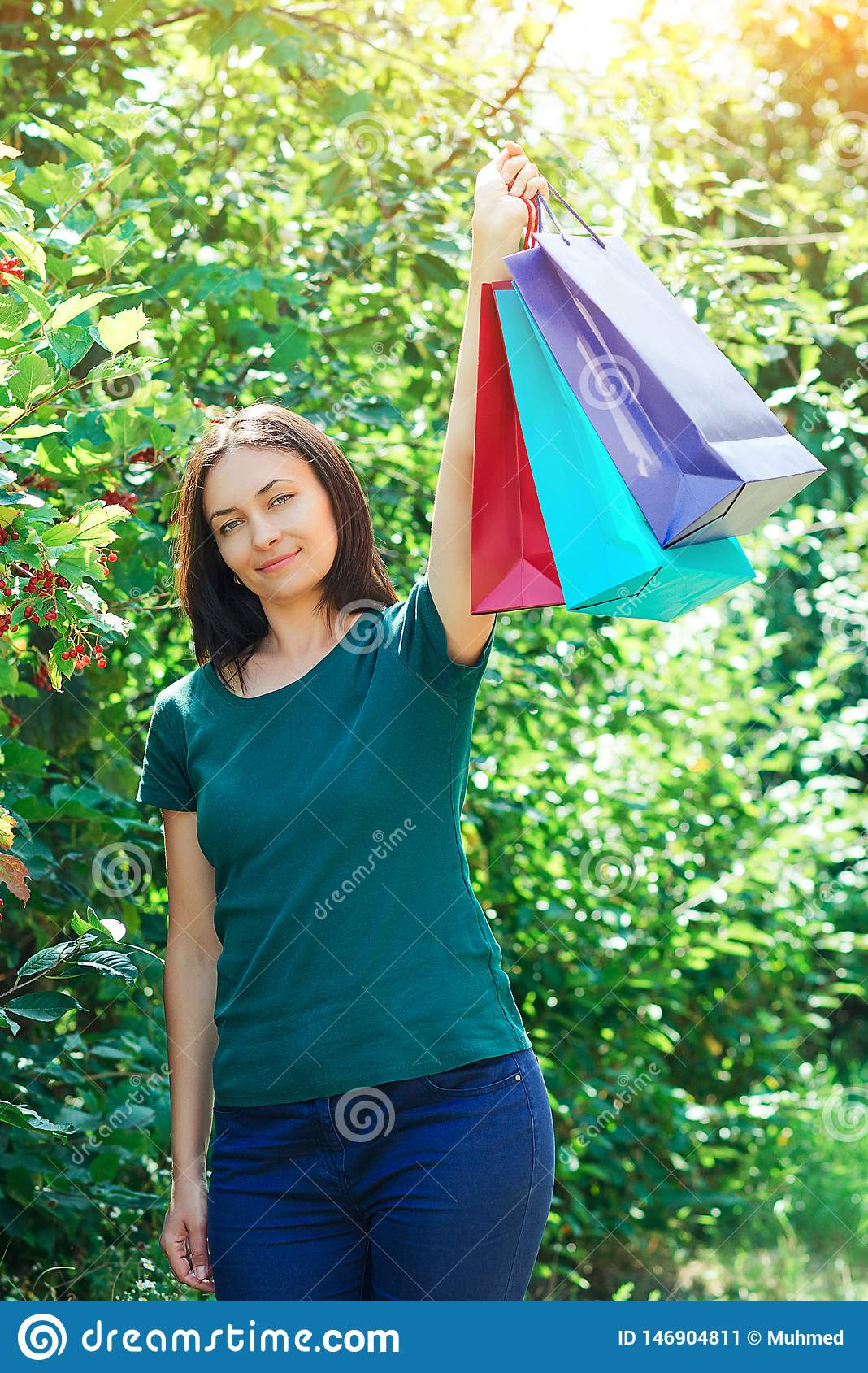 Happy brunette woman after great shopping sales, holding up colorful shopping bags