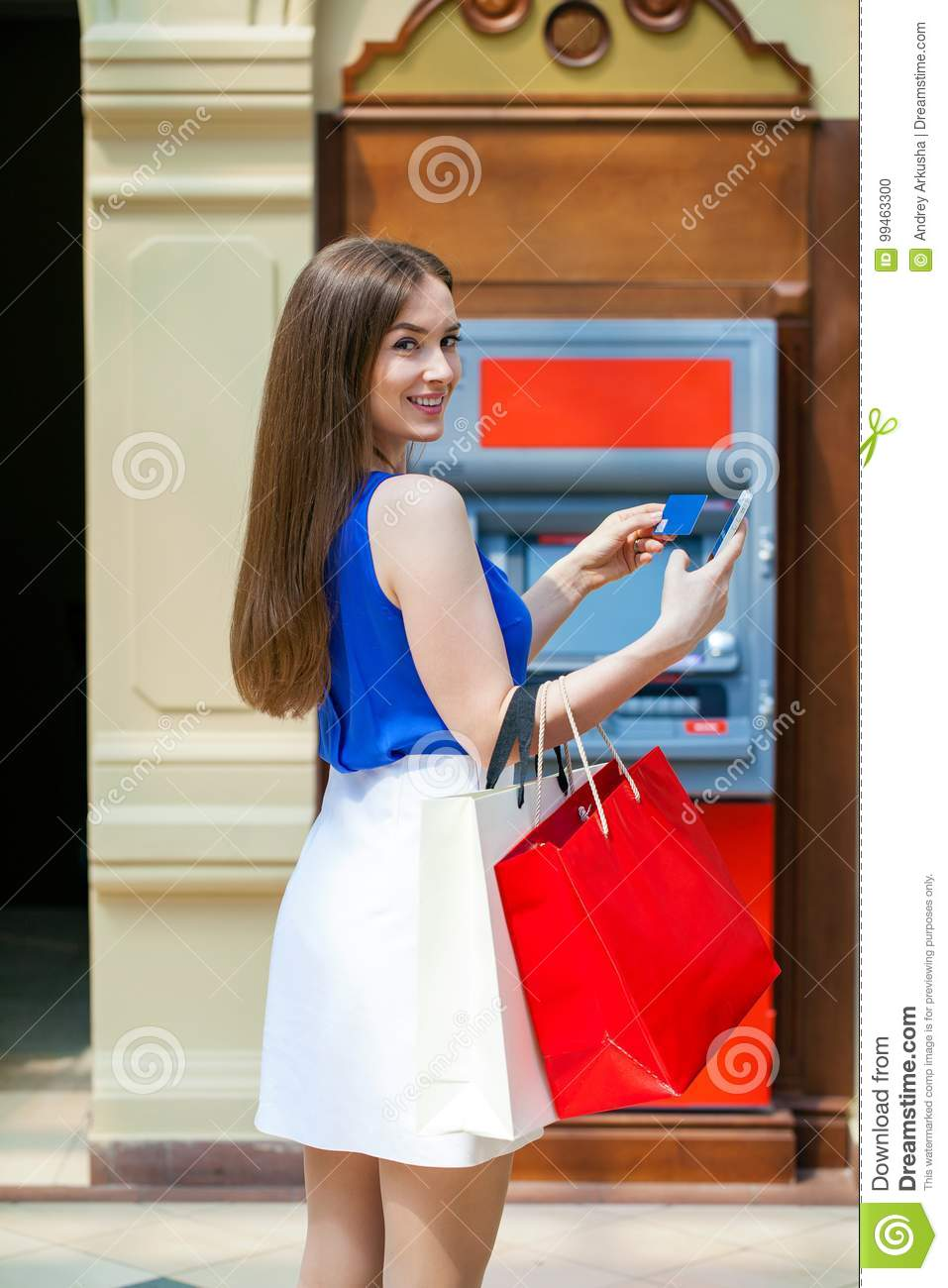 6008f47552b5 Young happy brunette woman withdrawing money from credit card at ATM,  indoor shop