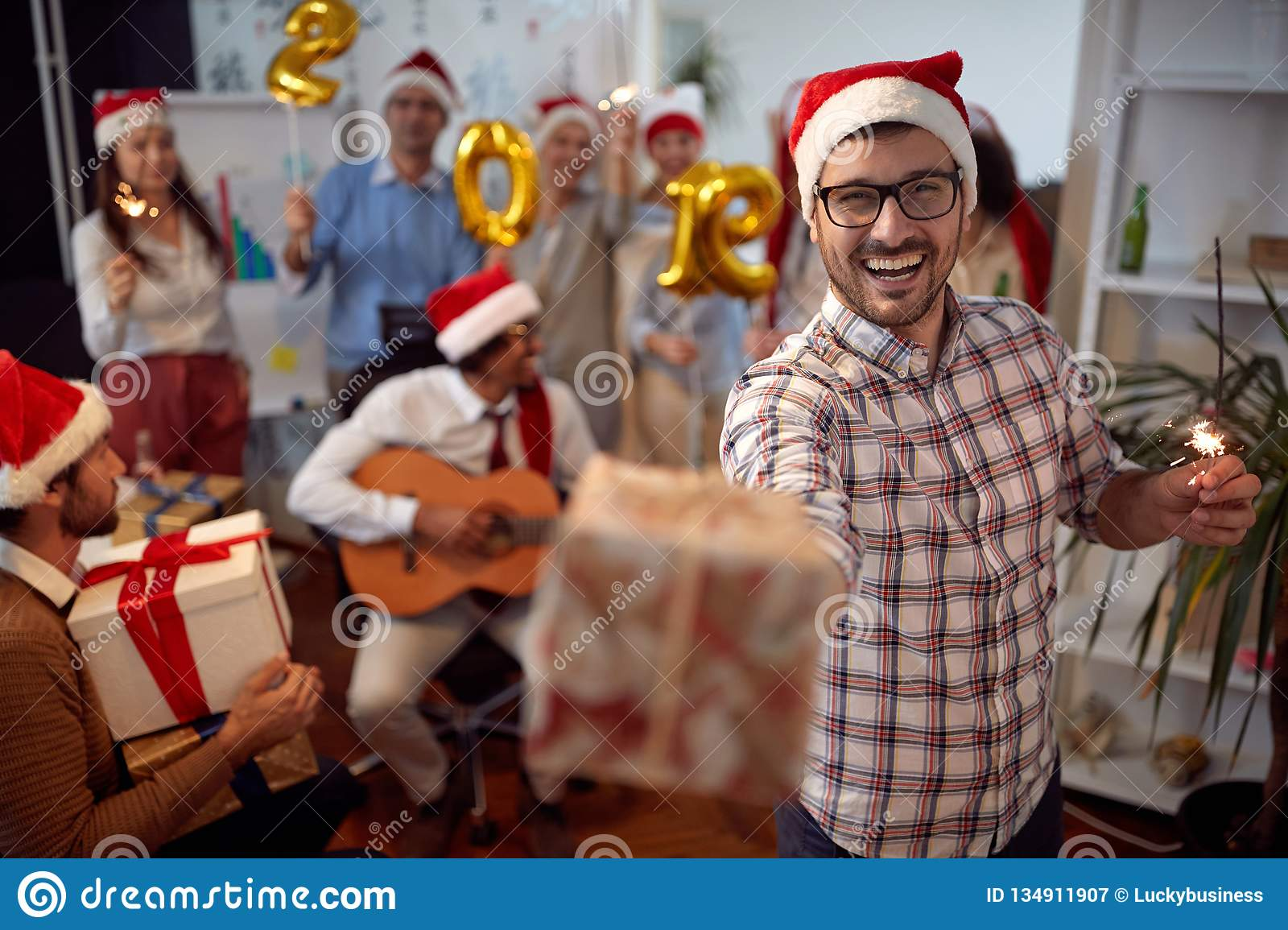 Happy business man have fun in Santa hat and exchange gifts at Xmas party with his colleagues