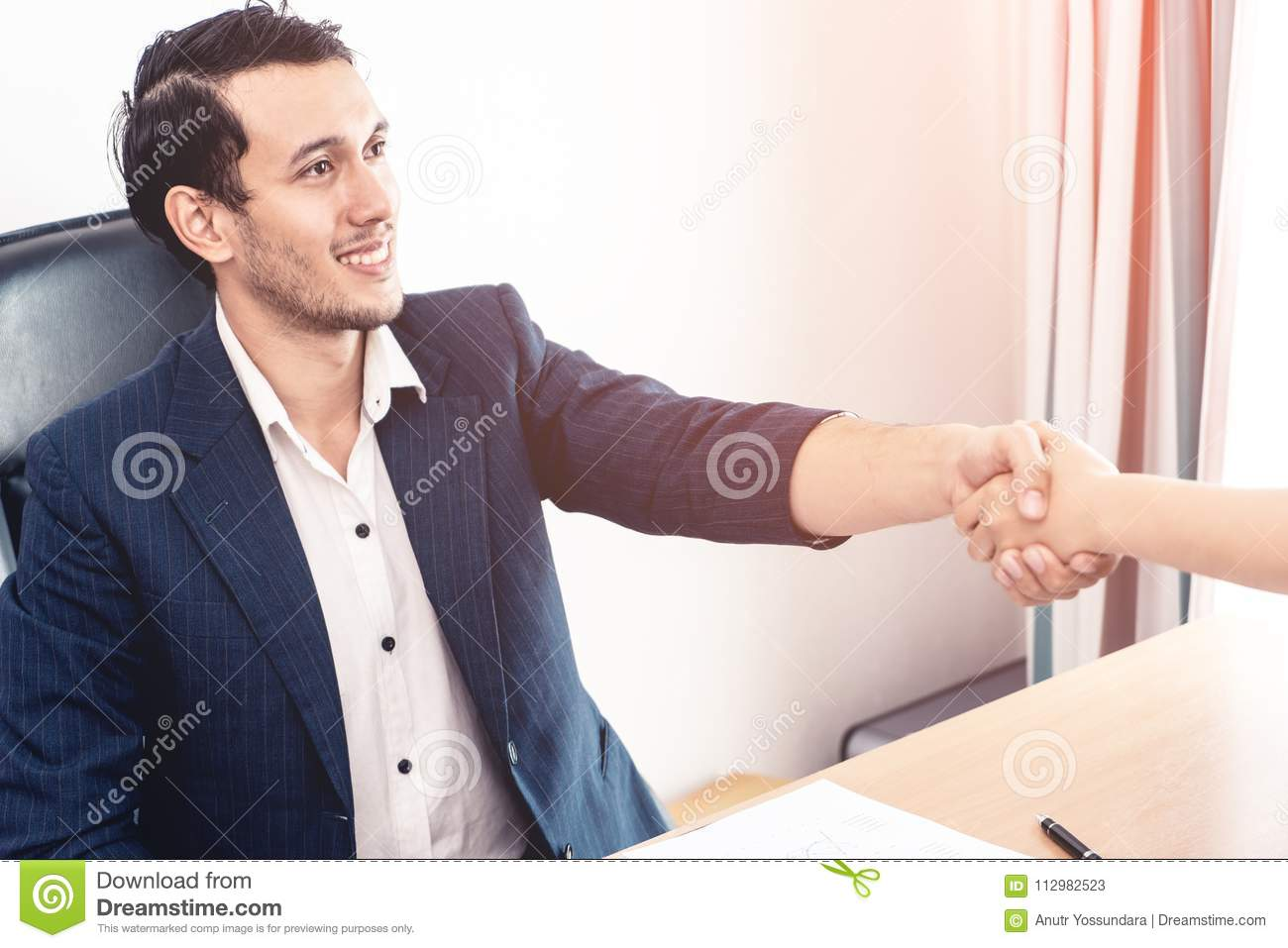 Happy business man shaking hand closing the deal