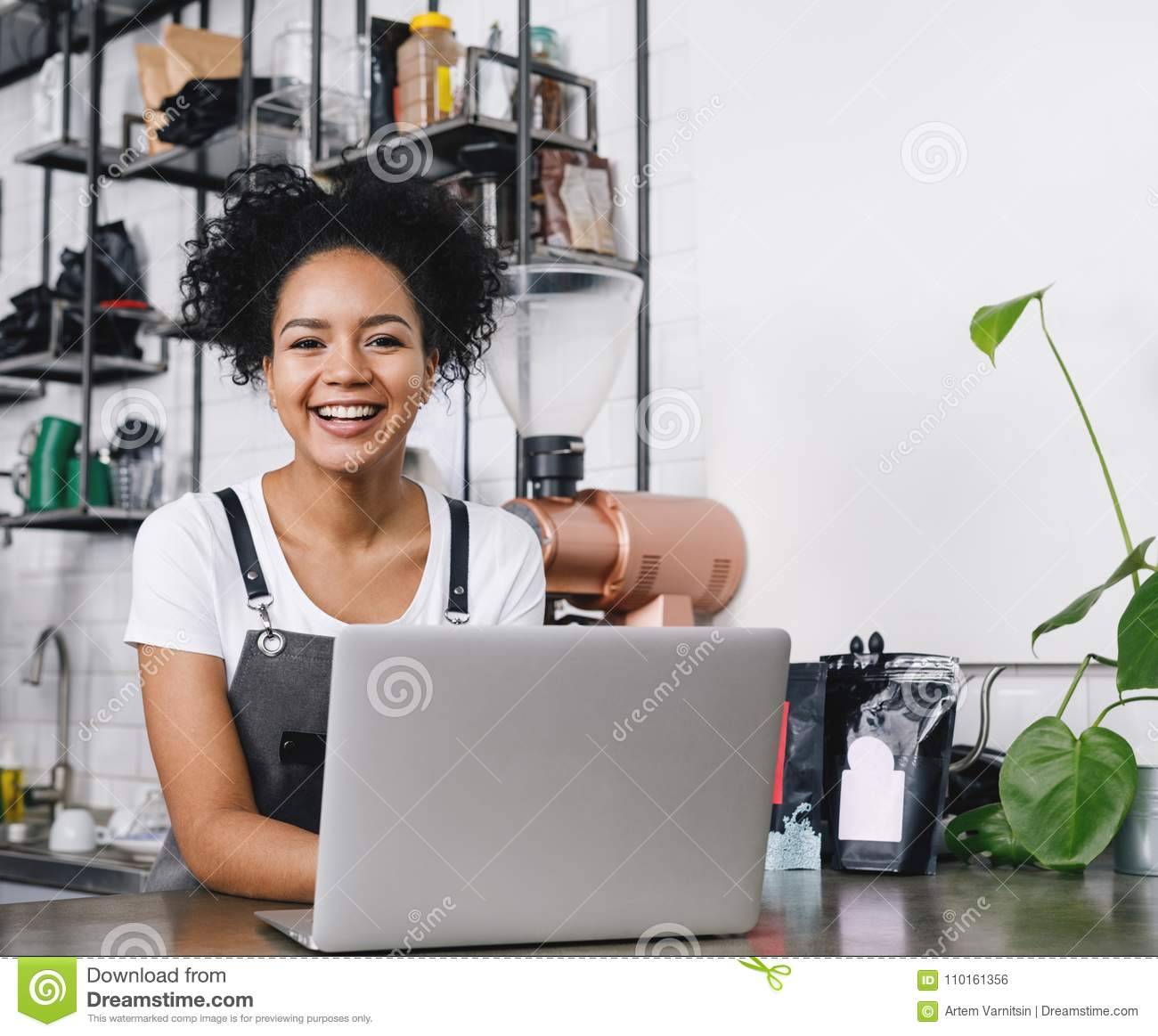 Happy business owner standing at counter