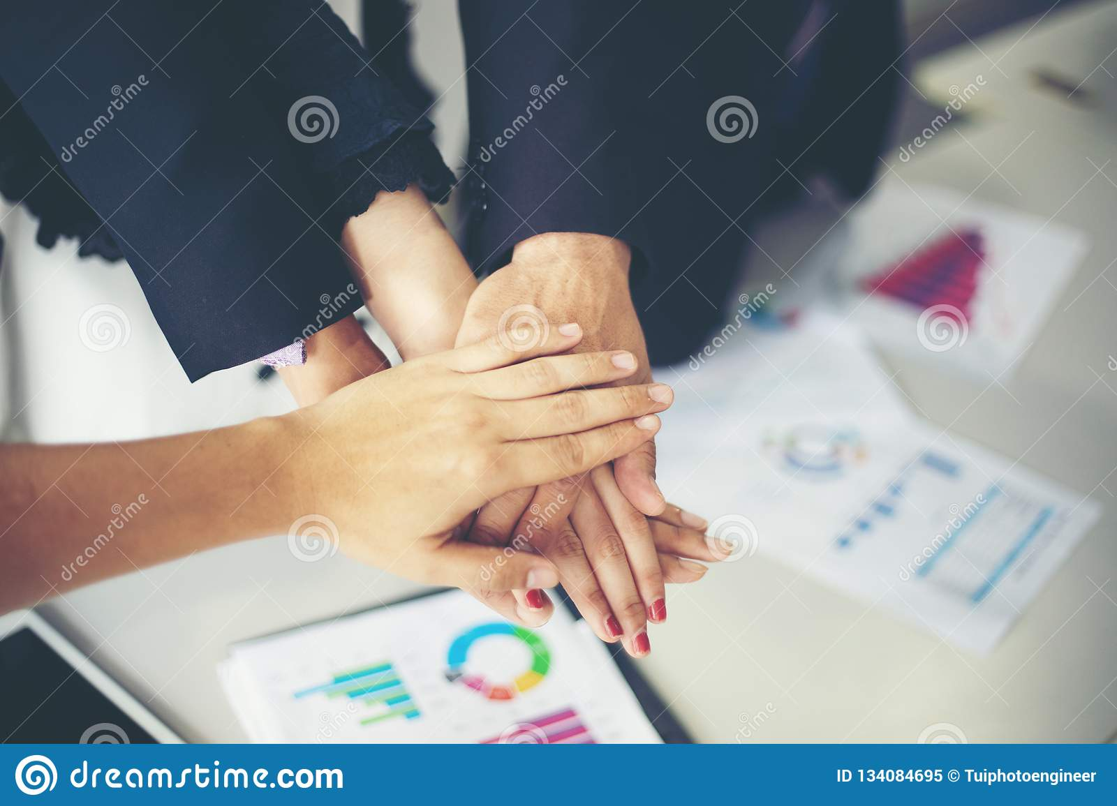 Happy Business people showing team work and giving five after signing agreement or contract with foreign partners in office