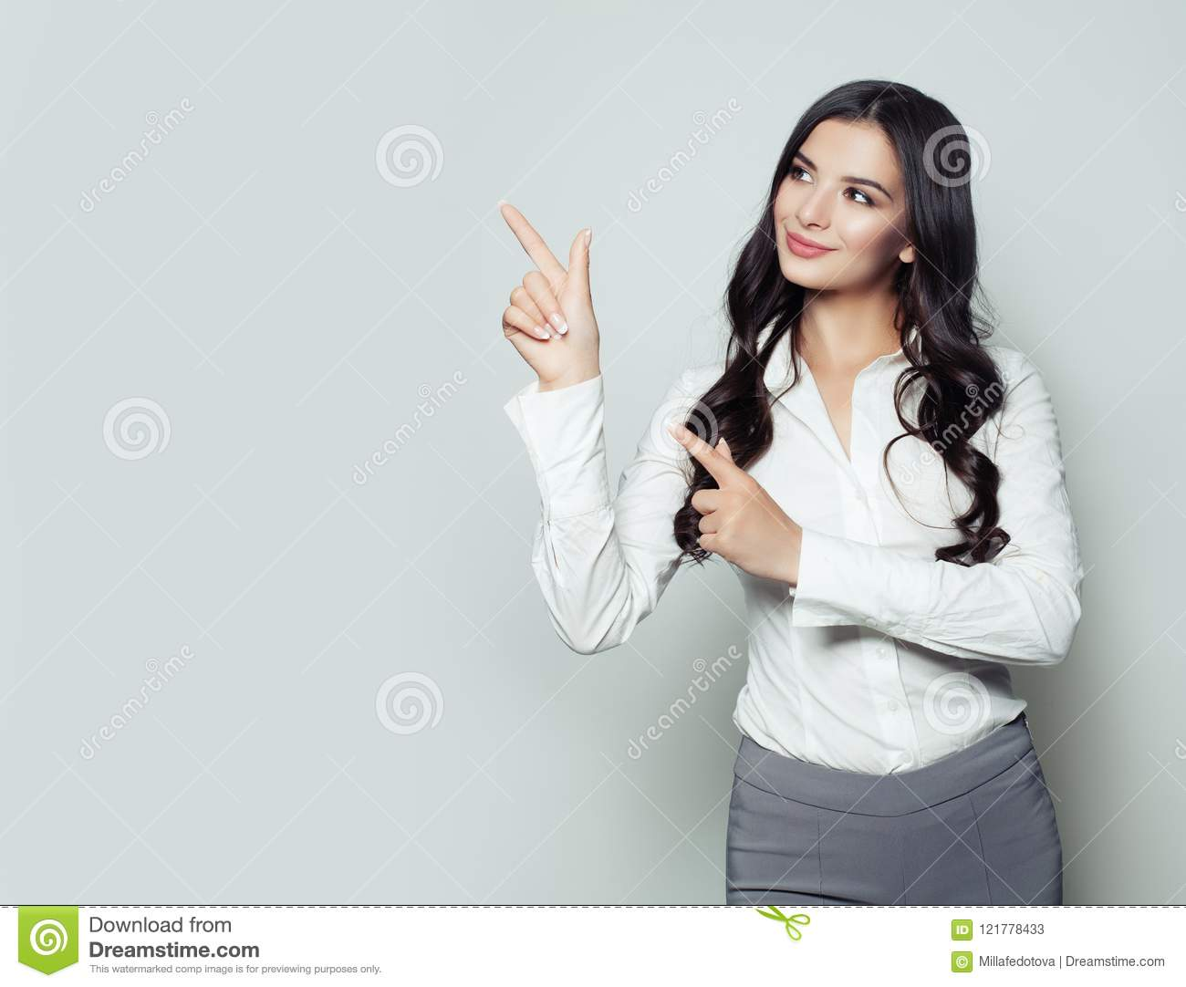 Happy business woman pointing her finger to empty copy space
