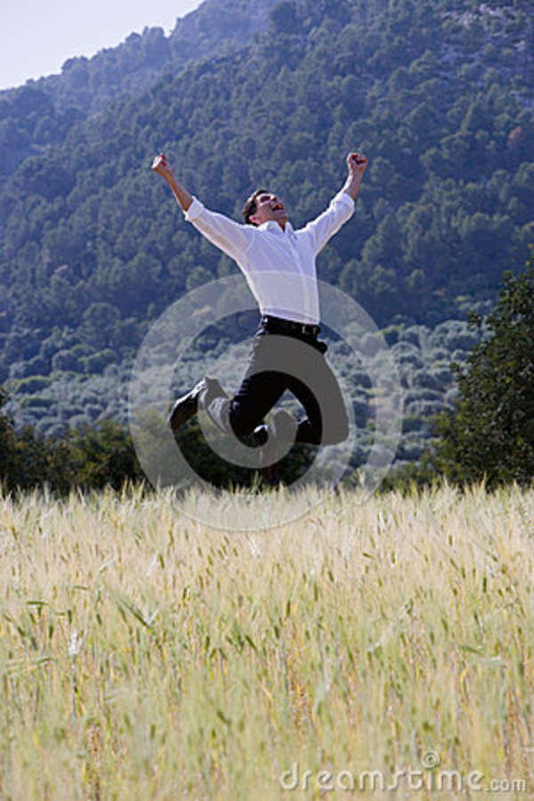 Happy businessman jumping with arms outstretched in rural field