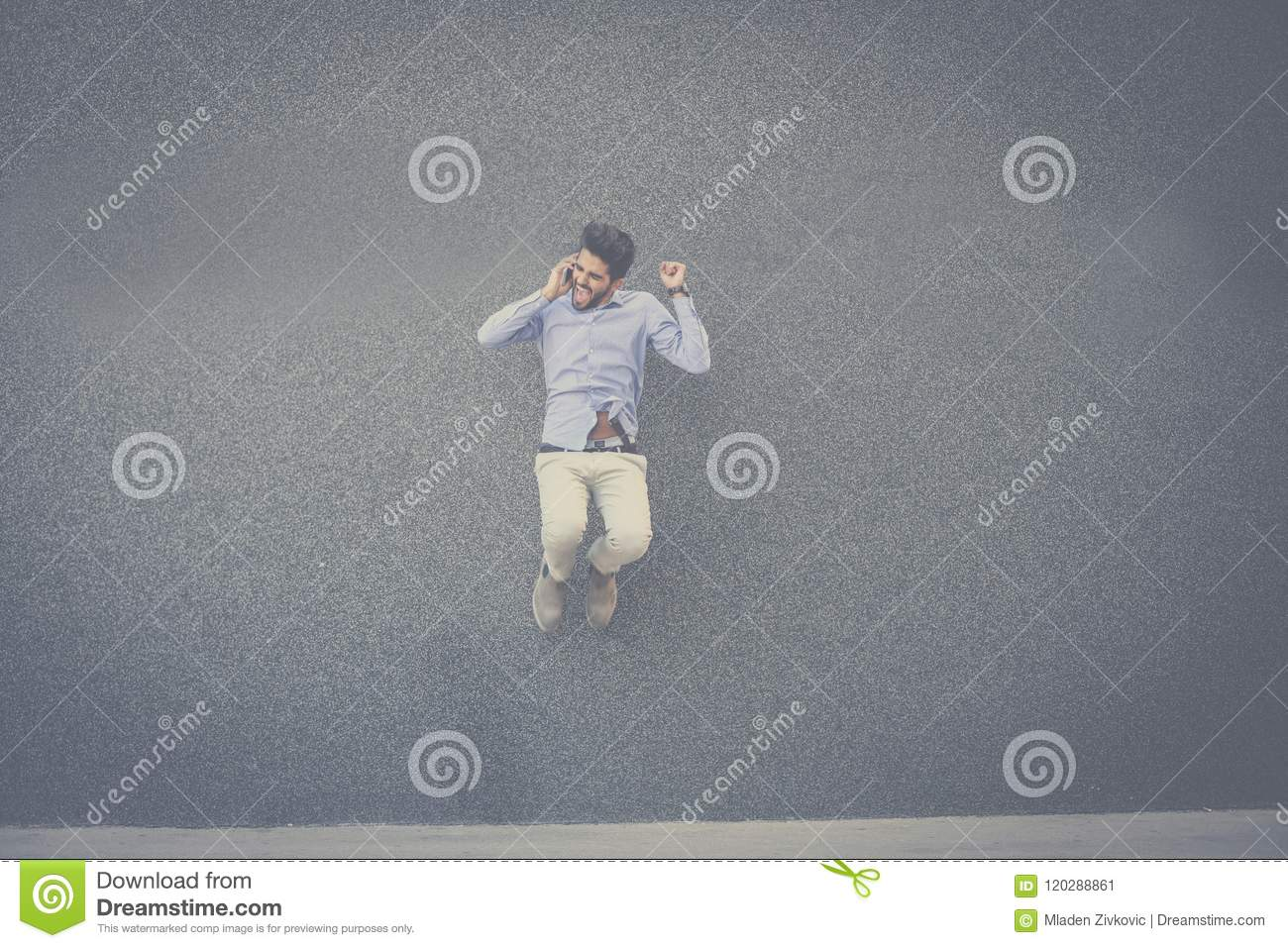 Happy businessman jumping and talking on smart phone.
