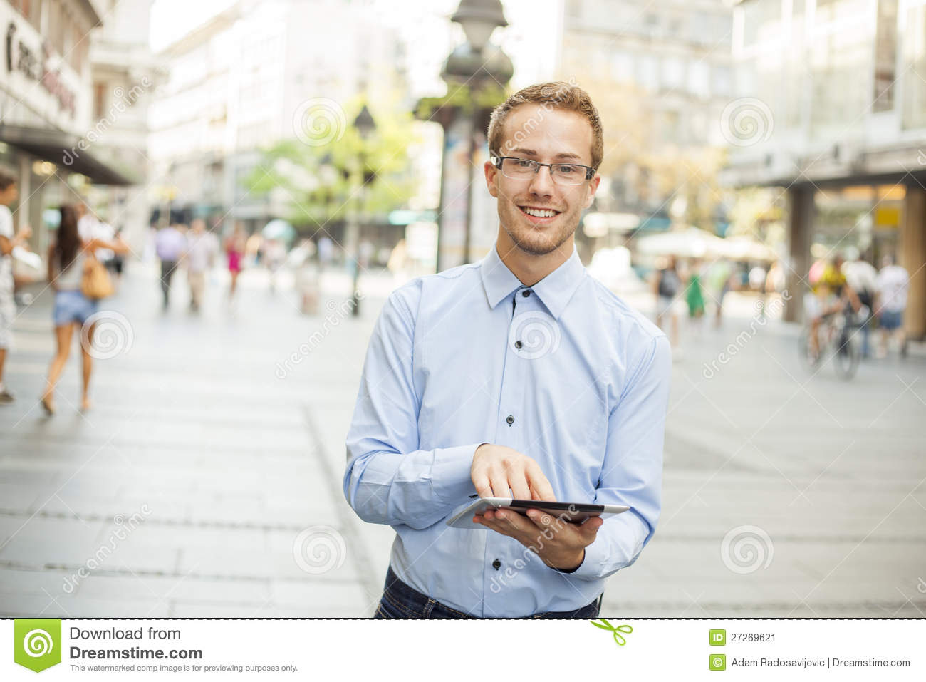Happy Businessman with tablet walking on street
