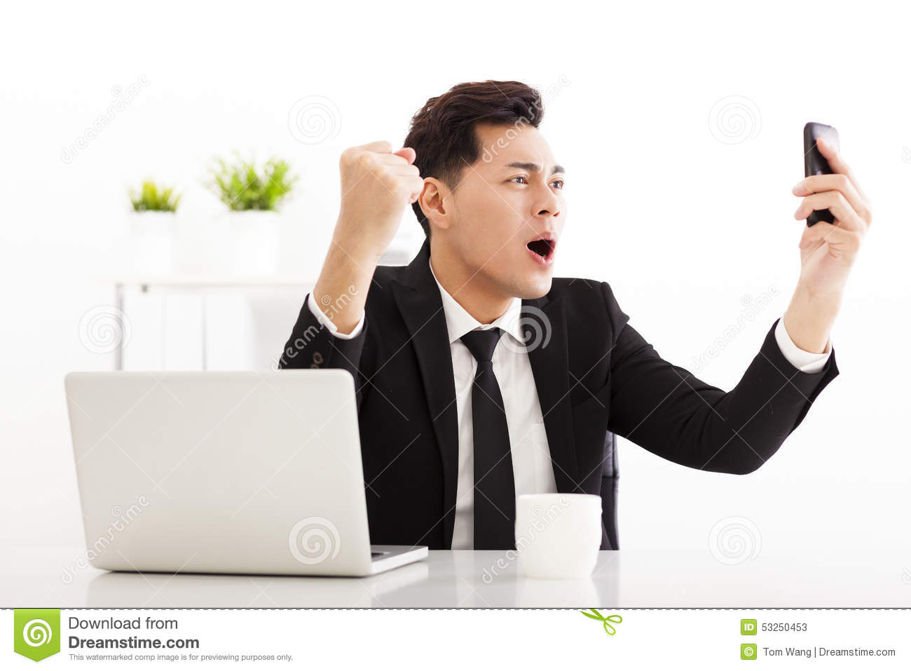 happy businessman watching the smart phone in office stock photo happy businessman watching the smart phone in office
