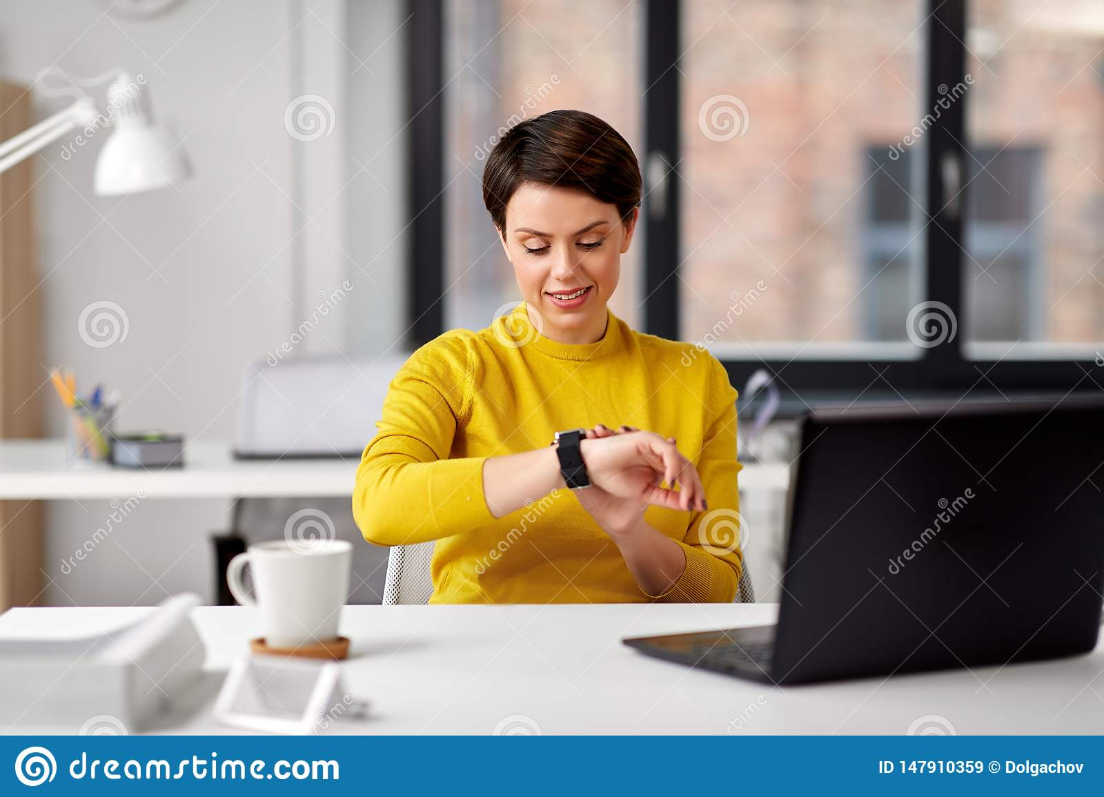 Happy businesswoman using smart watch at office