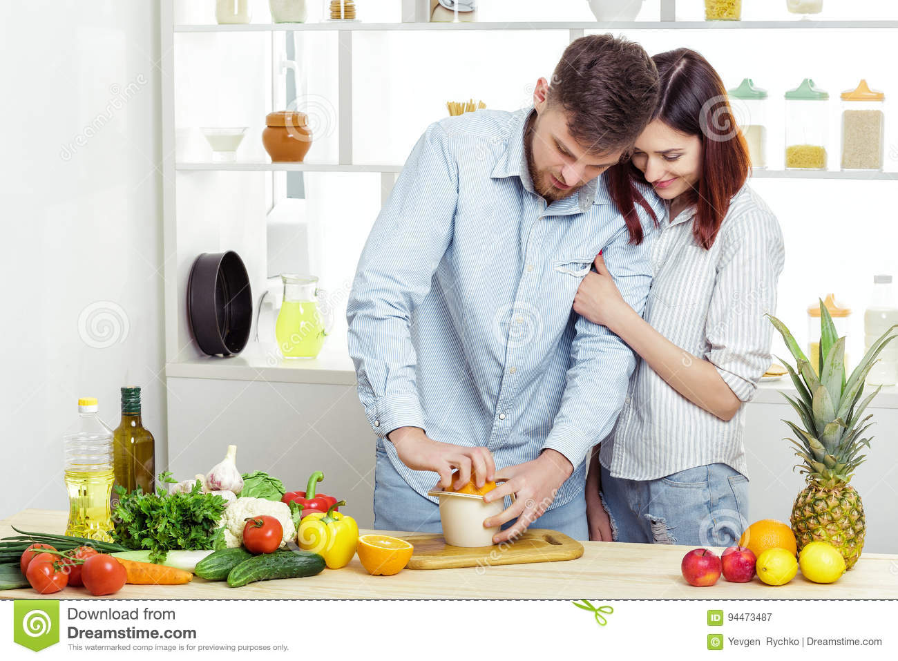 Happy c ouple in love in kitchen making healthy juice from fresh orange