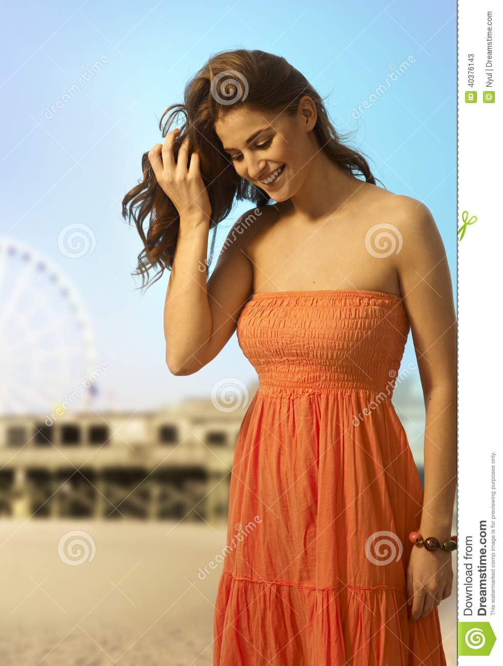 Happy casual woman at the beach looking down