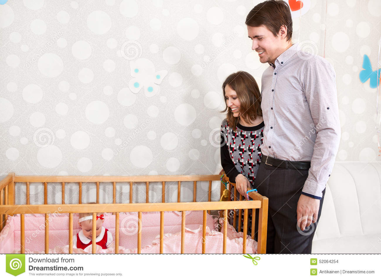 Baby bed with parents - Happy Caucasian Parents Standing Near Baby Bed And Looking At Child