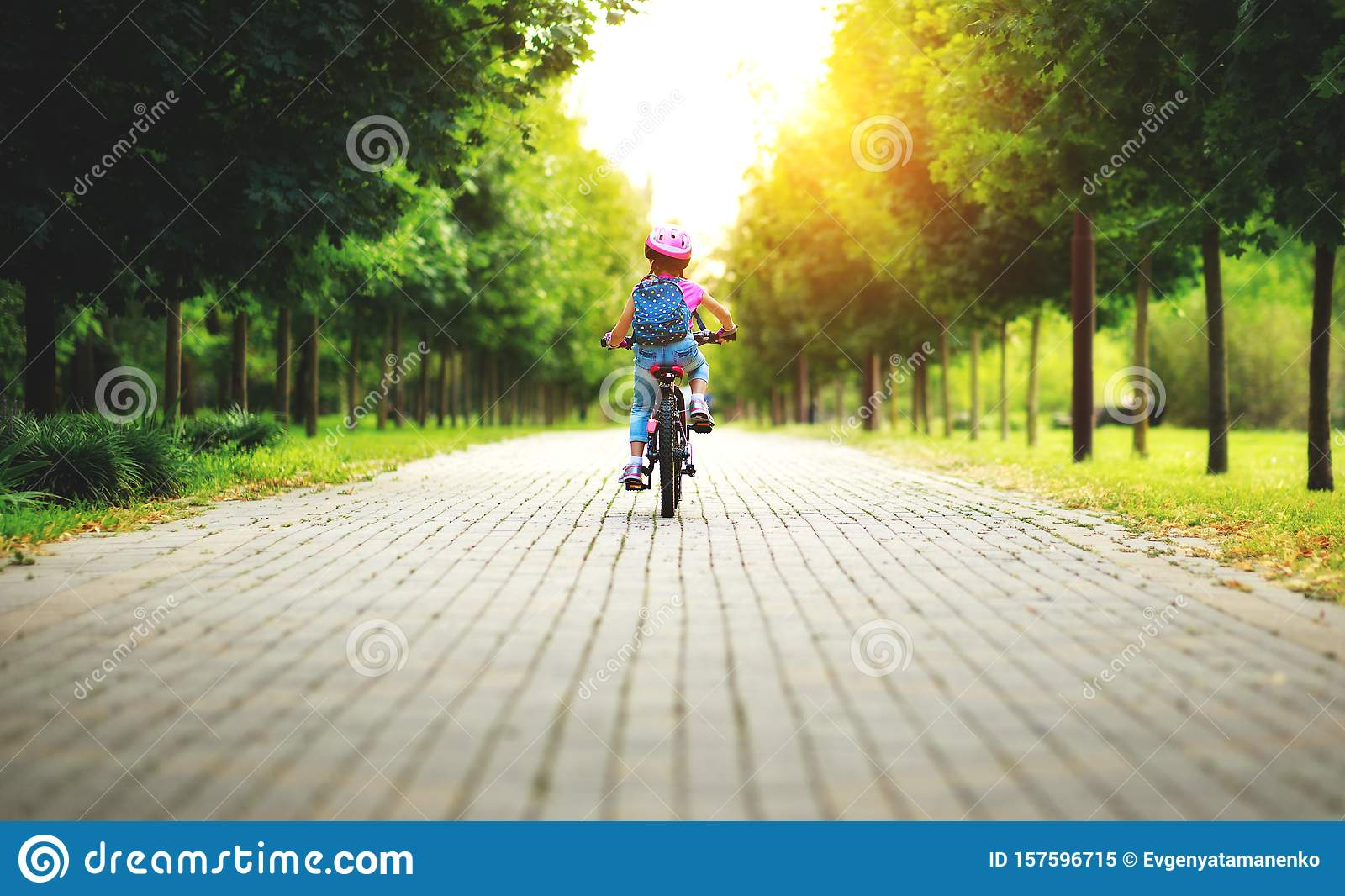 Happy cheerful child girl riding a bike in Park in nature