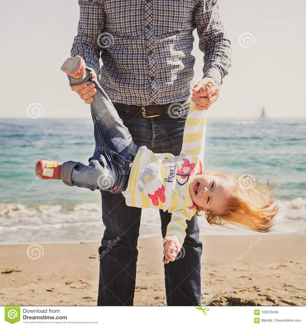 Young Happy Beautiful Family Playing Together On The Beach: Upside Down Daughter Royalty-Free Stock Photography
