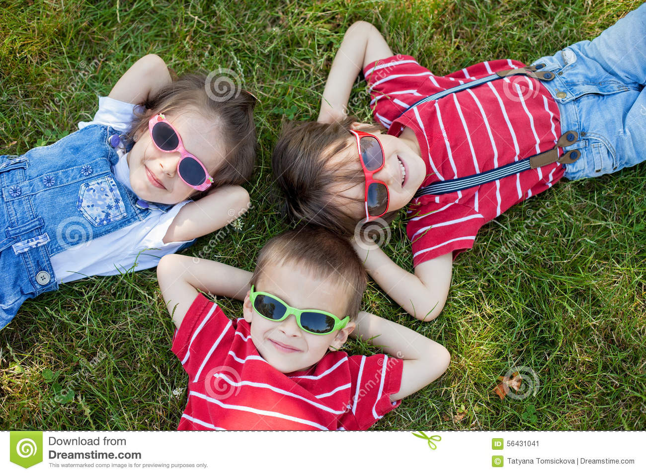 Happy cheerful smiling children, laying on a grass, wearing sung